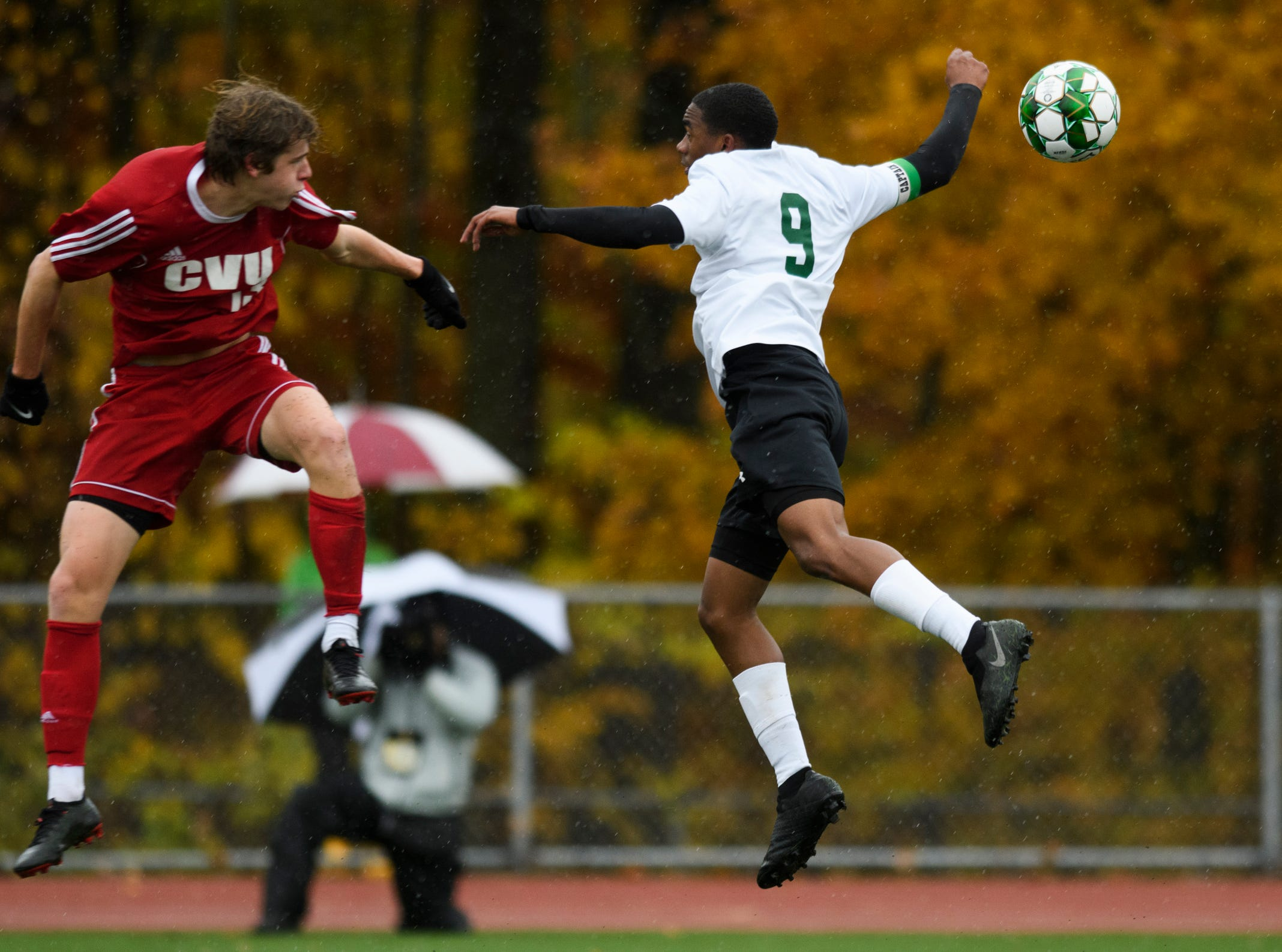 CVU's Erik Stolen (13) and St. Johnsbury's Malik Joell (9) battle to head the ball during the Division I boys soccer championship game between the St. Johnsbury Hilltoppers and the Champlain Valley Union Redhawks at Buck Hard Field on Saturday morning November 3, 2018 in Burlington.