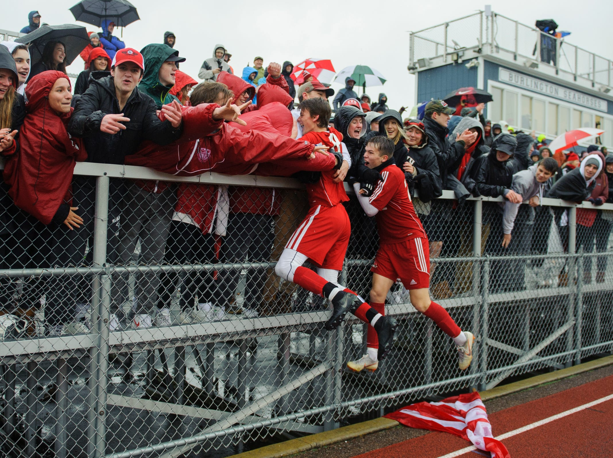 CVU celebrates with the fans during the Division I boys soccer championship game between the St. Johnsbury Hilltoppers and the Champlain Valley Union Redhawks at Buck Hard Field on Saturday morning November 3, 2018 in Burlington.