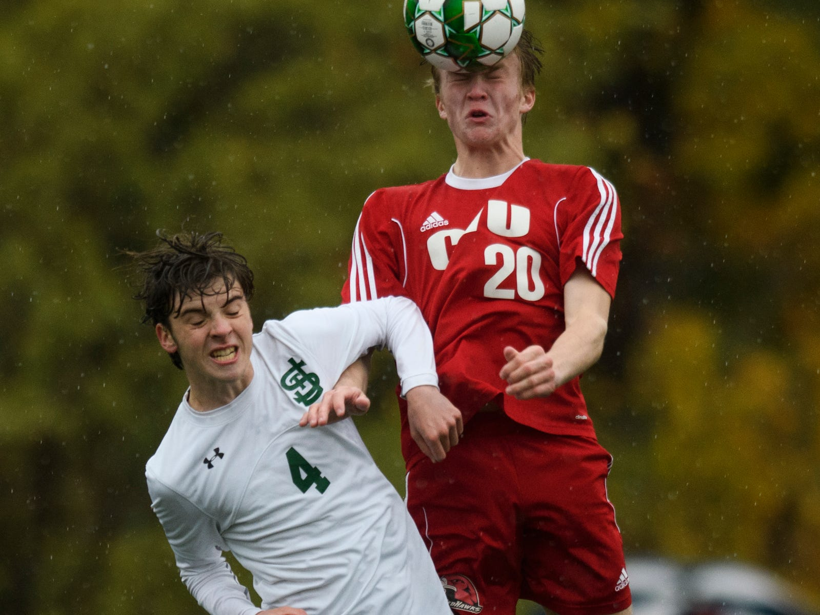 CVU's Nathan Godbout (20) leaps over St. Johnsbury's Joe Brady (4) to head the ball during the Division I boys soccer championship game between the St. Johnsbury Hilltoppers and the Champlain Valley Union Redhawks at Buck Hard Field on Saturday morning November 3, 2018 in Burlington.