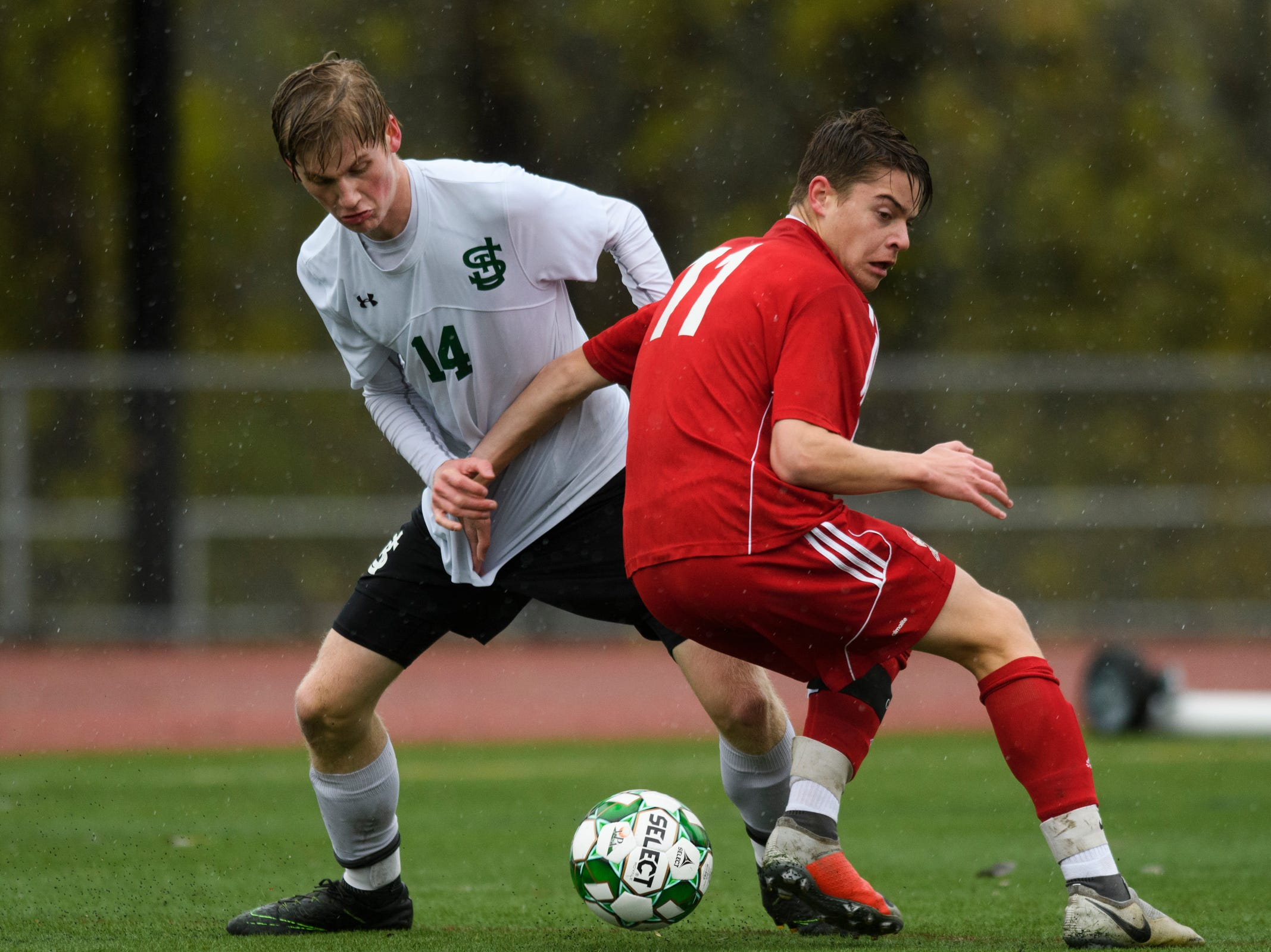 St. Johnsbury's Liam Tobin (14) battles for the ball with CVU's Caleb Martin (11) during the Division I boys soccer championship game between the St. Johnsbury Hilltoppers and the Champlain Valley Union Redhawks at Buck Hard Field on Saturday morning November 3, 2018 in Burlington.