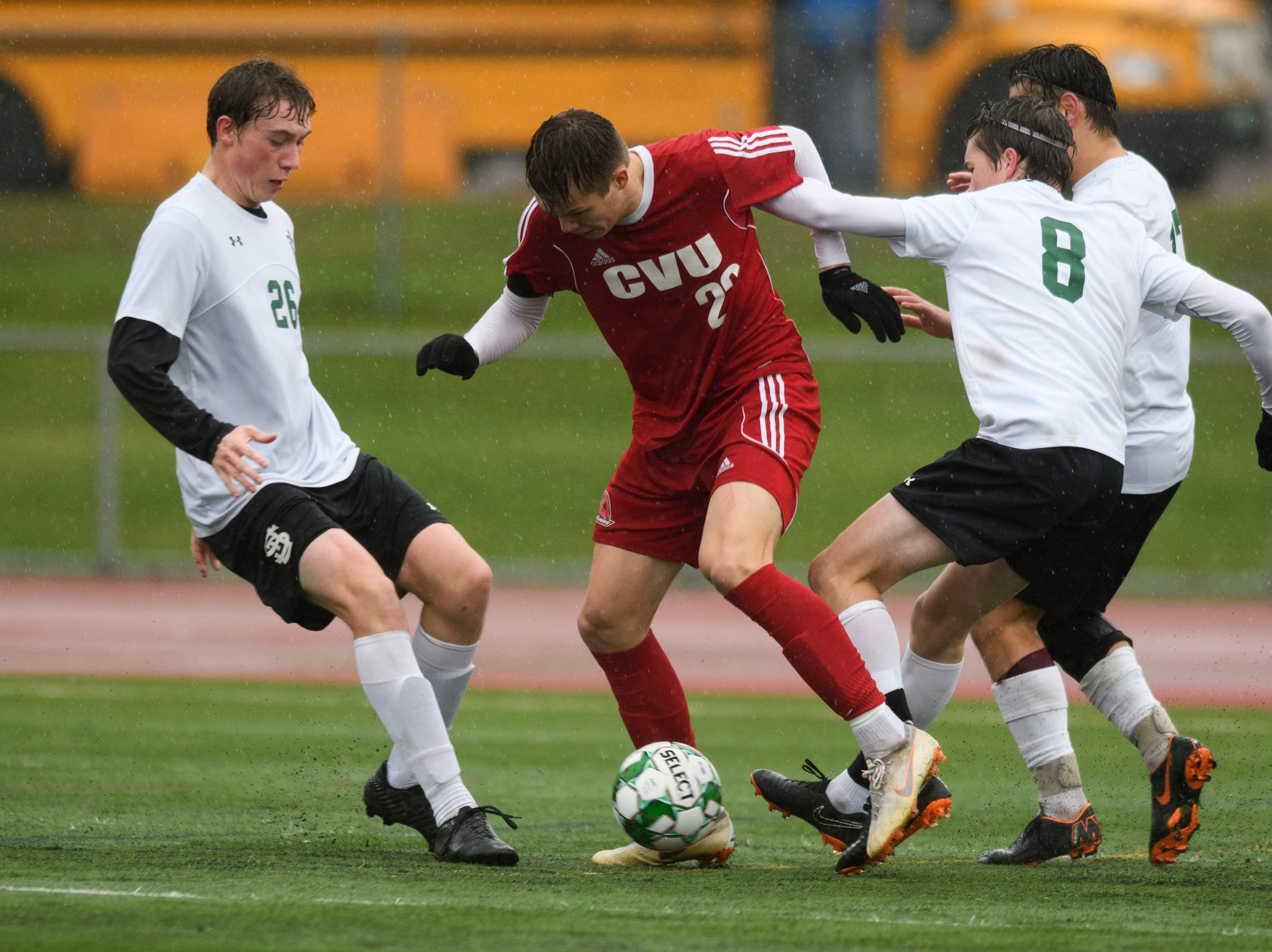 CVU's Jami Lashua (22) battles for the ball with St. Johnsbury's Thomas Zschau (8), Max Whitchurch (26) and Alex Gingue (17) during the Division I boys soccer championship game between the St. Johnsbury Hilltoppers and the Champlain Valley Union Redhawks at Buck Hard Field on Saturday morning November 3, 2018 in Burlington.
