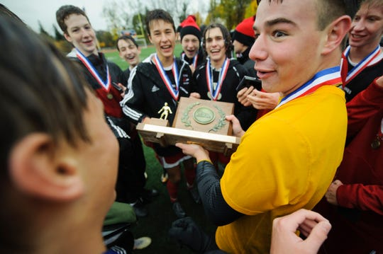 CVU goalie Aidan Johnson holds the championship trophy as the team looks on during the Division I boys soccer championship game between the St. Johnsbury Hilltoppers and the Champlain Valley Union Redhawks at Buck Hard Field on Saturday morning November 3, 2018 in Burlington.