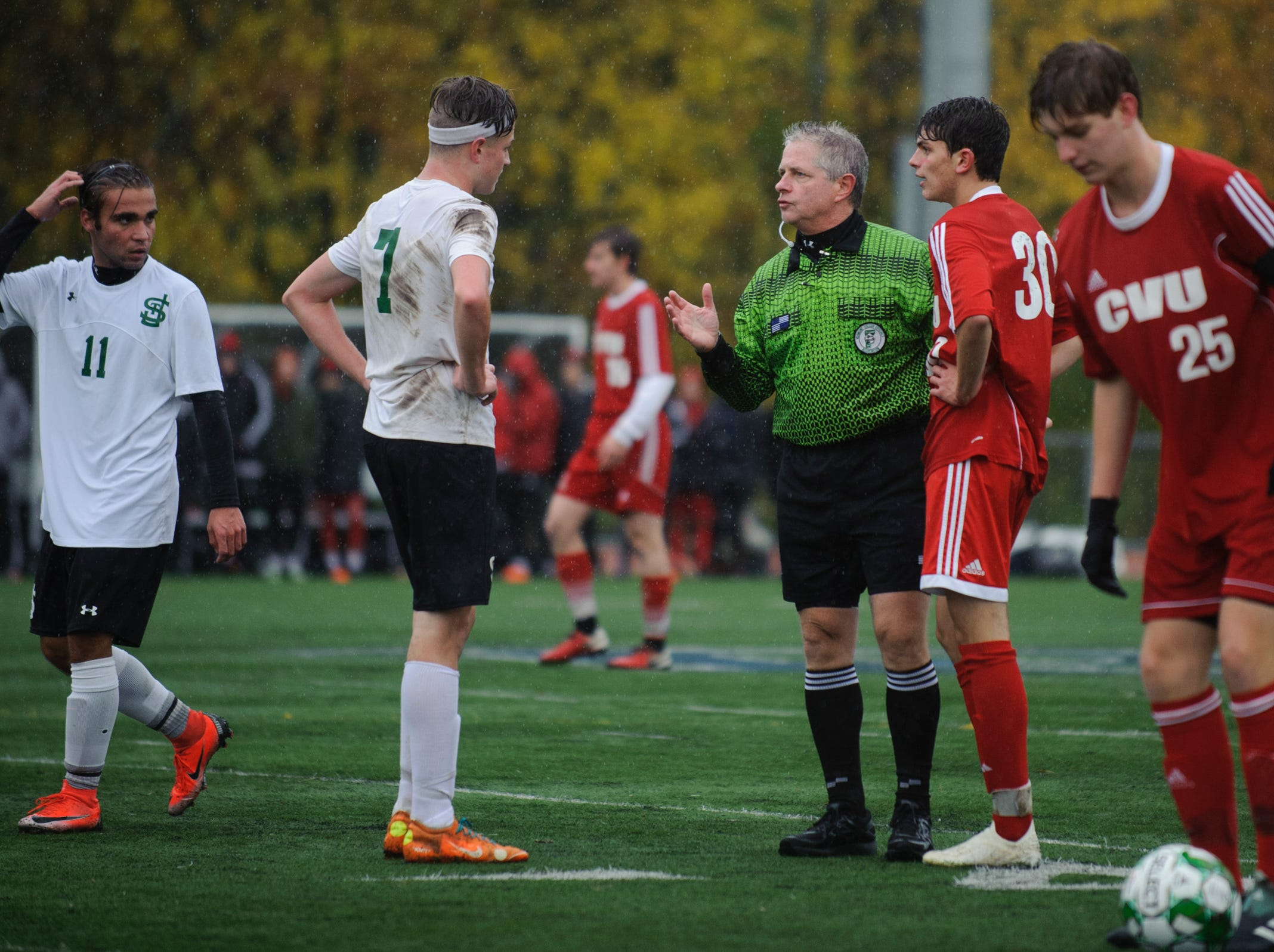 The referee has a talk with St. Johnsbury's Konrad Tillman (7) and CVU's Jack Sinopoli (30) during the Division I boys soccer championship game between the St. Johnsbury Hilltoppers and the Champlain Valley Union Redhawks at Buck Hard Field on Saturday morning November 3, 2018 in Burlington. (