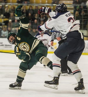 UVM #25 Matt Alvaro gets checked off the puck by Uconn #20 Wyatt Newpoer during their hockey game Friday night, Nov. 2, 2018, at home. The Huskies pulled out a win, 1-0.