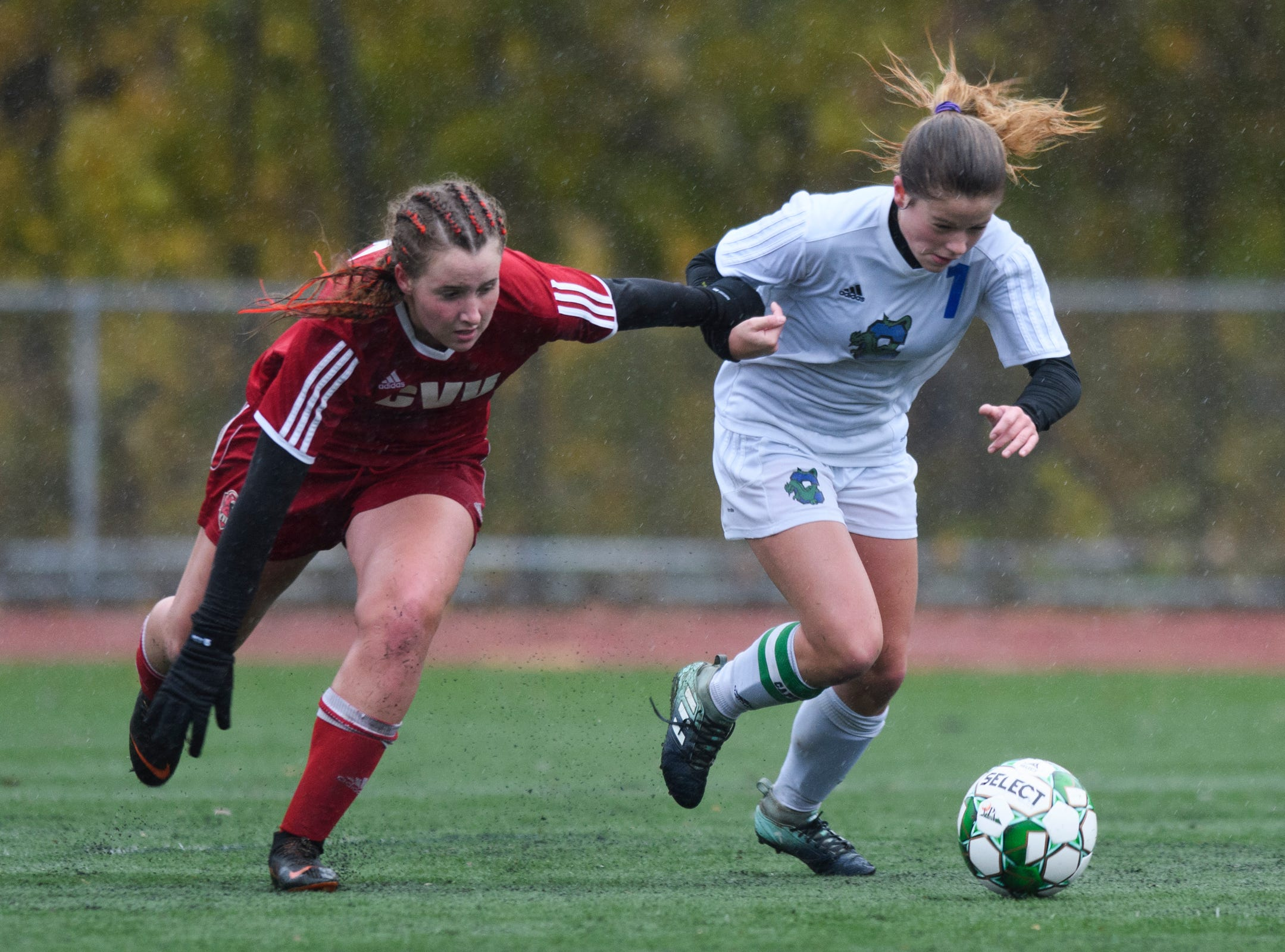 CVU's Olivia Morton (15) and Colchester's Madison Finelli (1) battle for the ball during the division I girls soccer championship game between the Colchester Lakers and the Champlain Valley Union Redhawks at Buck Hard Field on Saturday morning November 3, 2018 in Burlington.