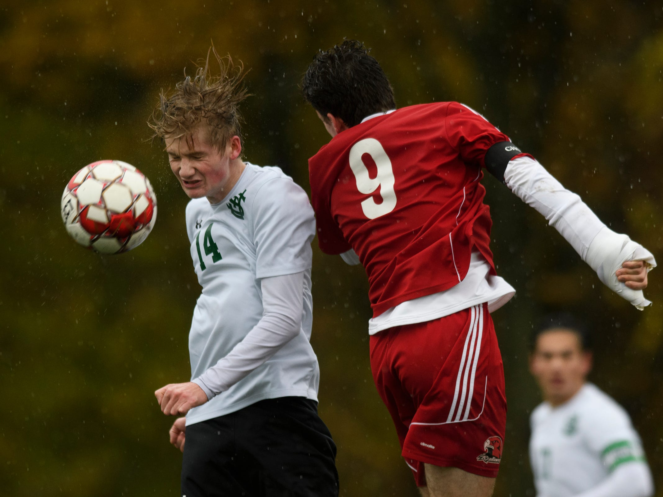 St. Johnsbury's Liam Tobin (14) and CVU's Jonah Roberts (9) battle to head the ball during the Division I boys soccer championship game between the St. Johnsbury Hilltoppers and the Champlain Valley Union Redhawks at Buck Hard Field on Saturday morning November 3, 2018 in Burlington.