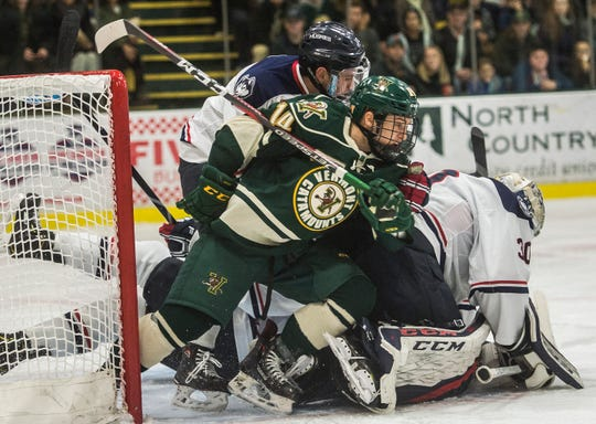 UVM #14 Ace Cowans piles onto Uconn goalie #30 Adam Huska after making the save during their hockey game Friday night, Nov. 2, 2018, at home. The Huskies pulled out a win, 1-0.