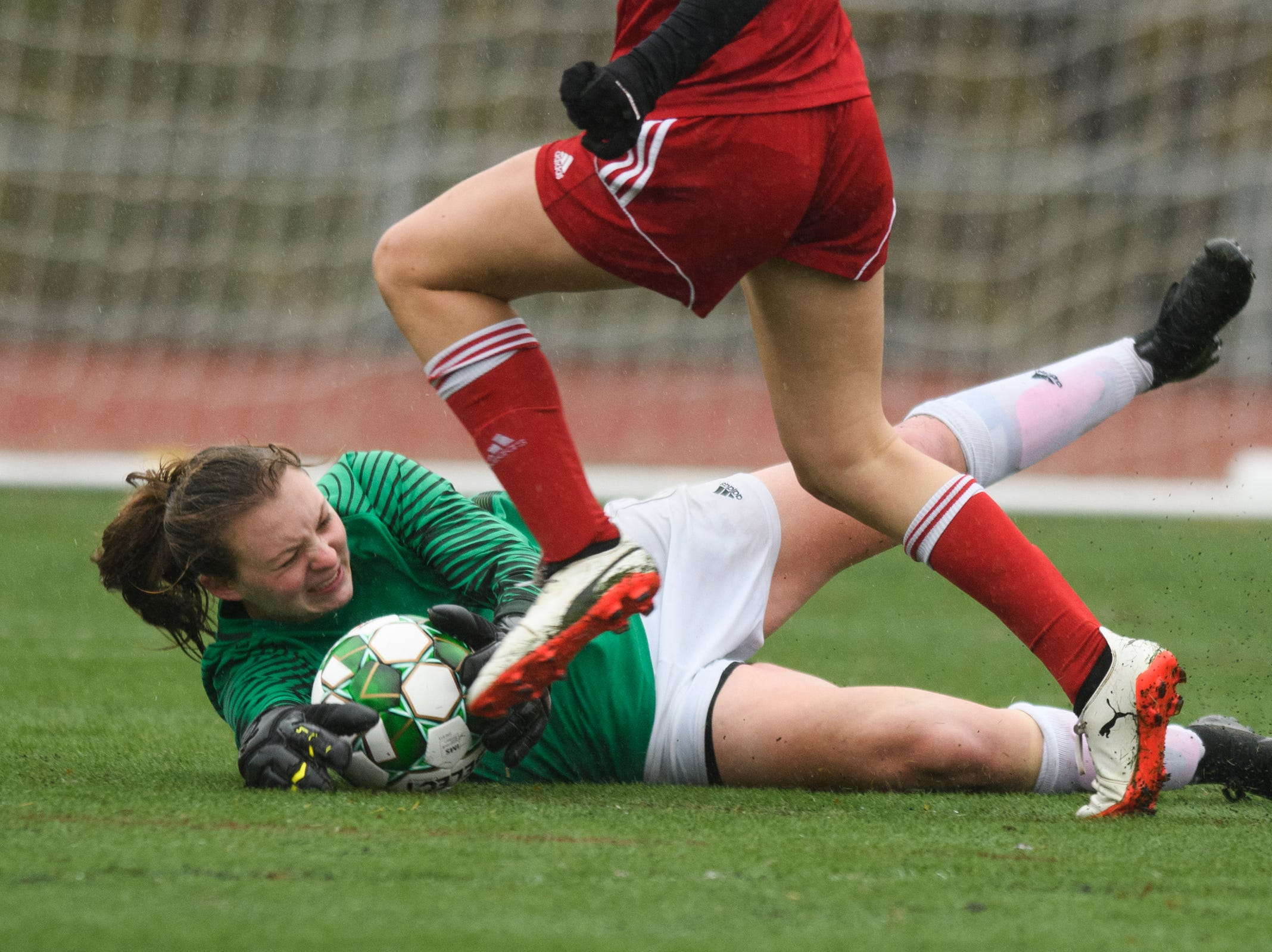 Colchester goalie Olivia Moore makes a diving save on a shot by CVU's Josie Pecor (22) during the division I girls soccer championship game between the Colchester Lakers and the Champlain Valley Union Redhawks at Buck Hard Field on Saturday morning November 3, 2018 in Burlington.