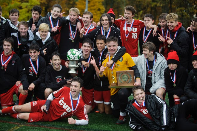 CVU poses for a photo with the championship trophy during the Division I boys soccer championship game between the St. Johnsbury Hilltoppers and the Champlain Valley Union Redhawks at Buck Hard Field on Saturday morning November 3, 2018 in Burlington.