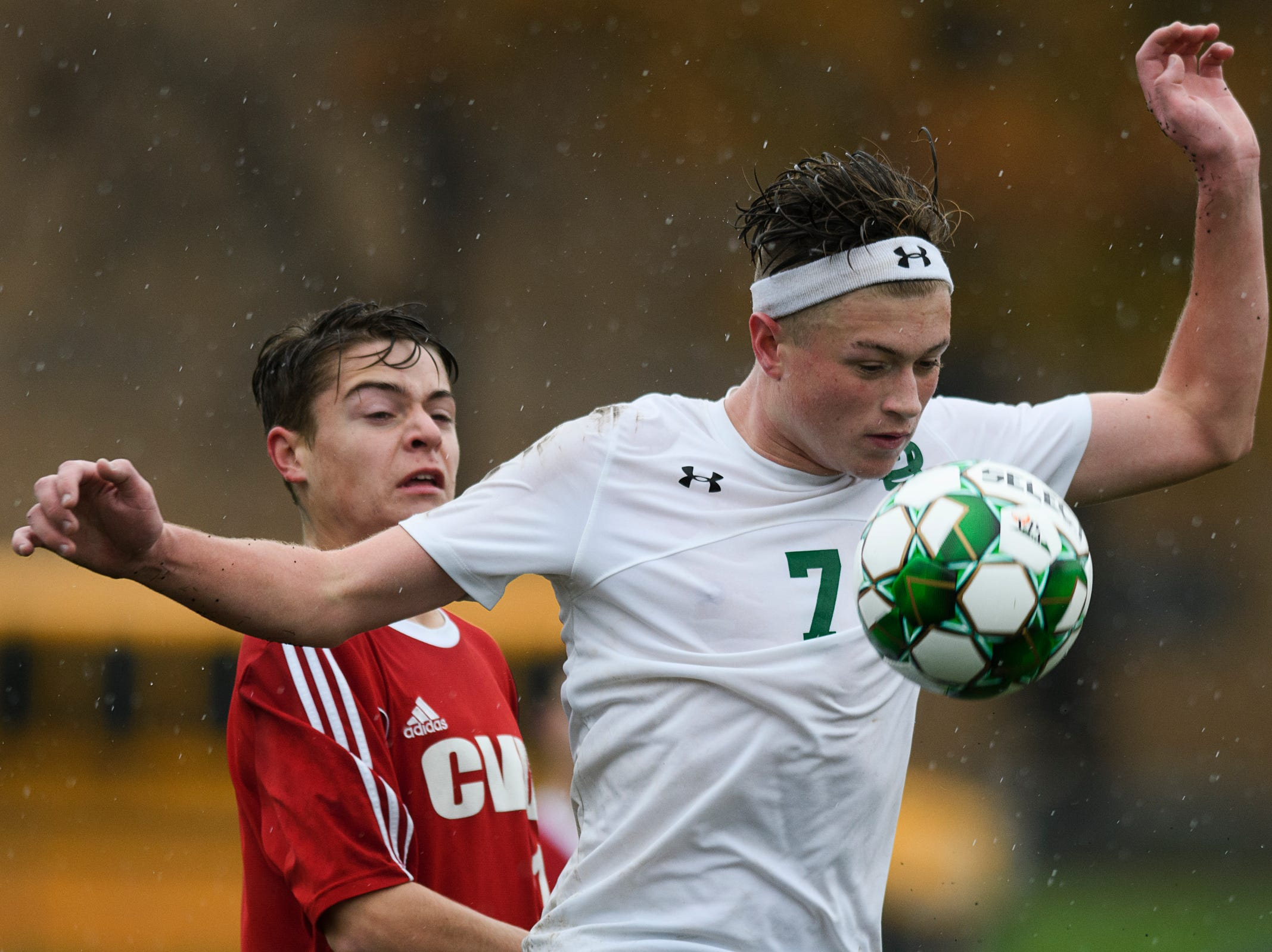 St. Johnsbury's Konrad Tillman (7) plays the ball in front of CVU's Caleb Martin during the Division I boys soccer championship game between the St. Johnsbury Hilltoppers and the Champlain Valley Union Redhawks at Buck Hard Field on Saturday morning November 3, 2018 in Burlington.