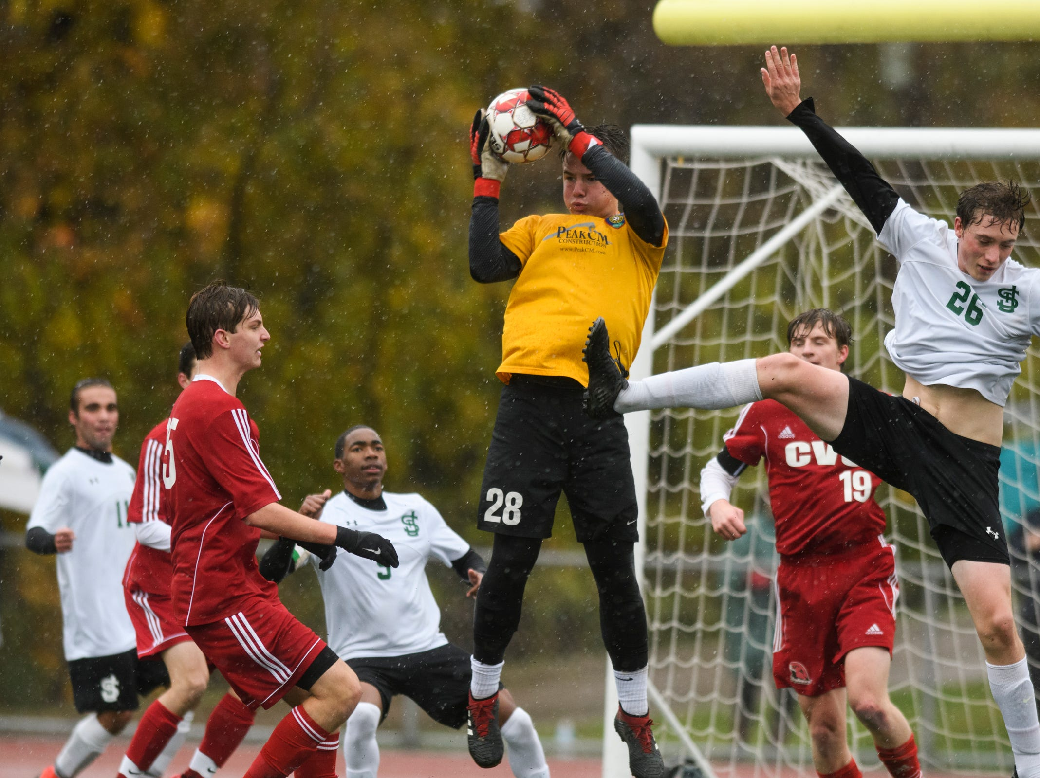 CVU goalie Aidan Johnson (28) leaps to make a save during the Division I boys soccer championship game between the St. Johnsbury Hilltoppers and the Champlain Valley Union Redhawks at Buck Hard Field on Saturday morning November 3, 2018 in Burlington.