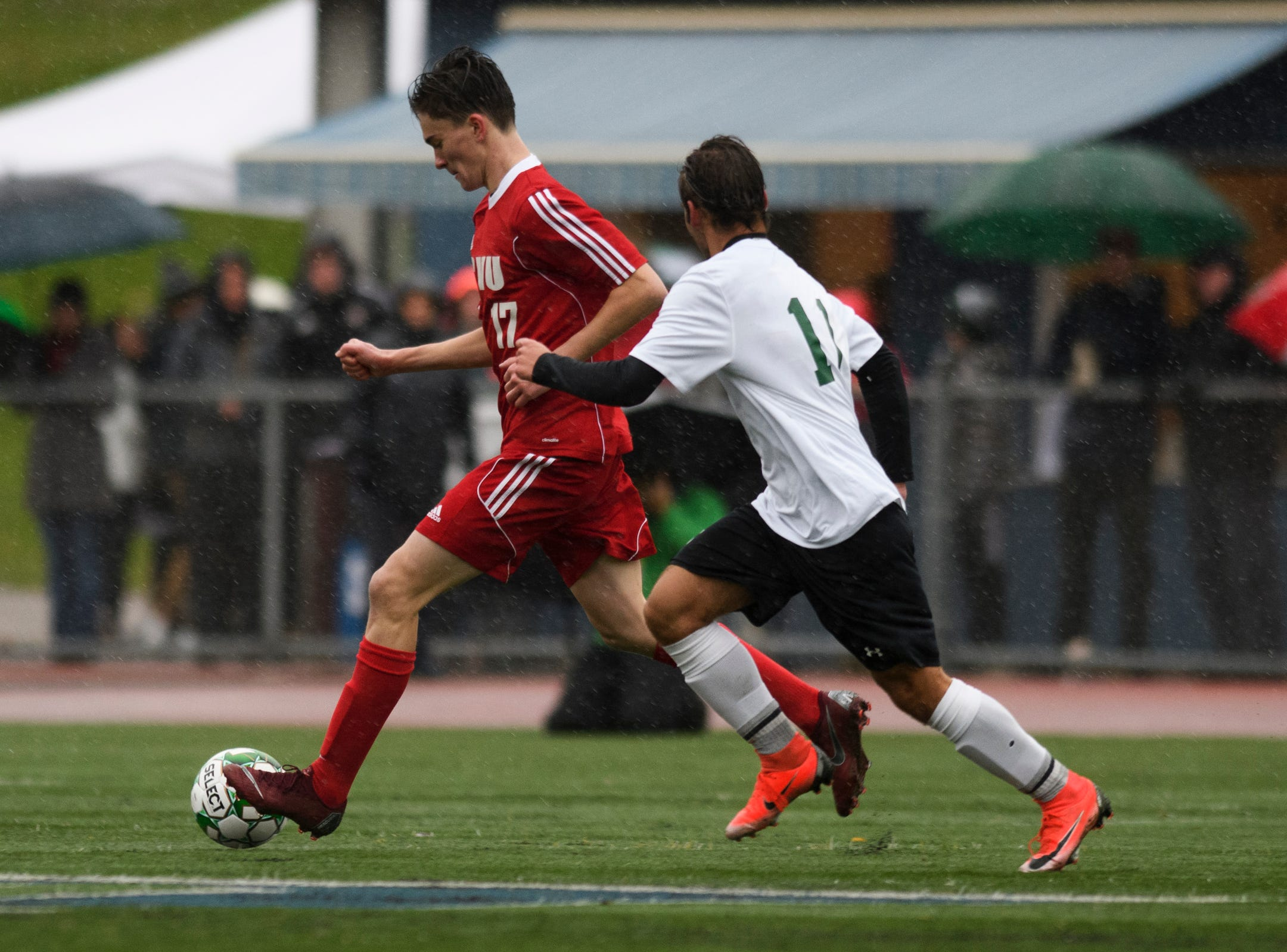 CVU's Nathaniel Sampson (17) runs past St, Johnsbury's Pablo Gonzalez-Rotger (11) with the ball during the Division I boys soccer championship game between the St. Johnsbury Hilltoppers and the Champlain Valley Union Redhawks at Buck Hard Field on Saturday morning November 3, 2018 in Burlington.