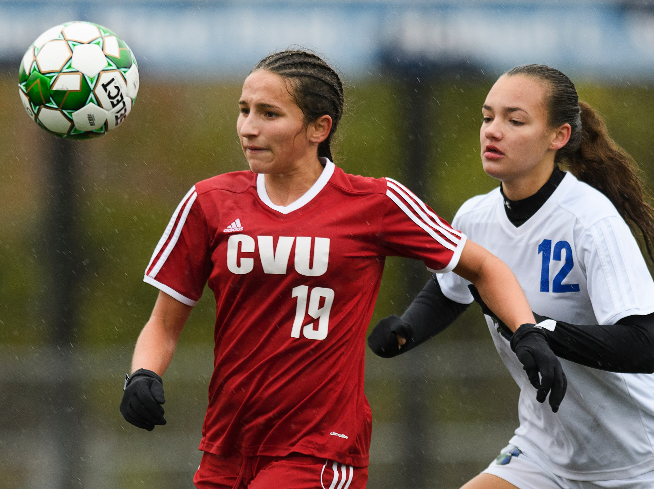 CVU's Sara Kelley (19) and Colchester's Jordan Clark (12) battle for the ball during the division I girls soccer championship game between the Colchester Lakers and the Champlain Valley Union Redhawks at Buck Hard Field on Saturday morning November 3, 2018 in Burlington.
