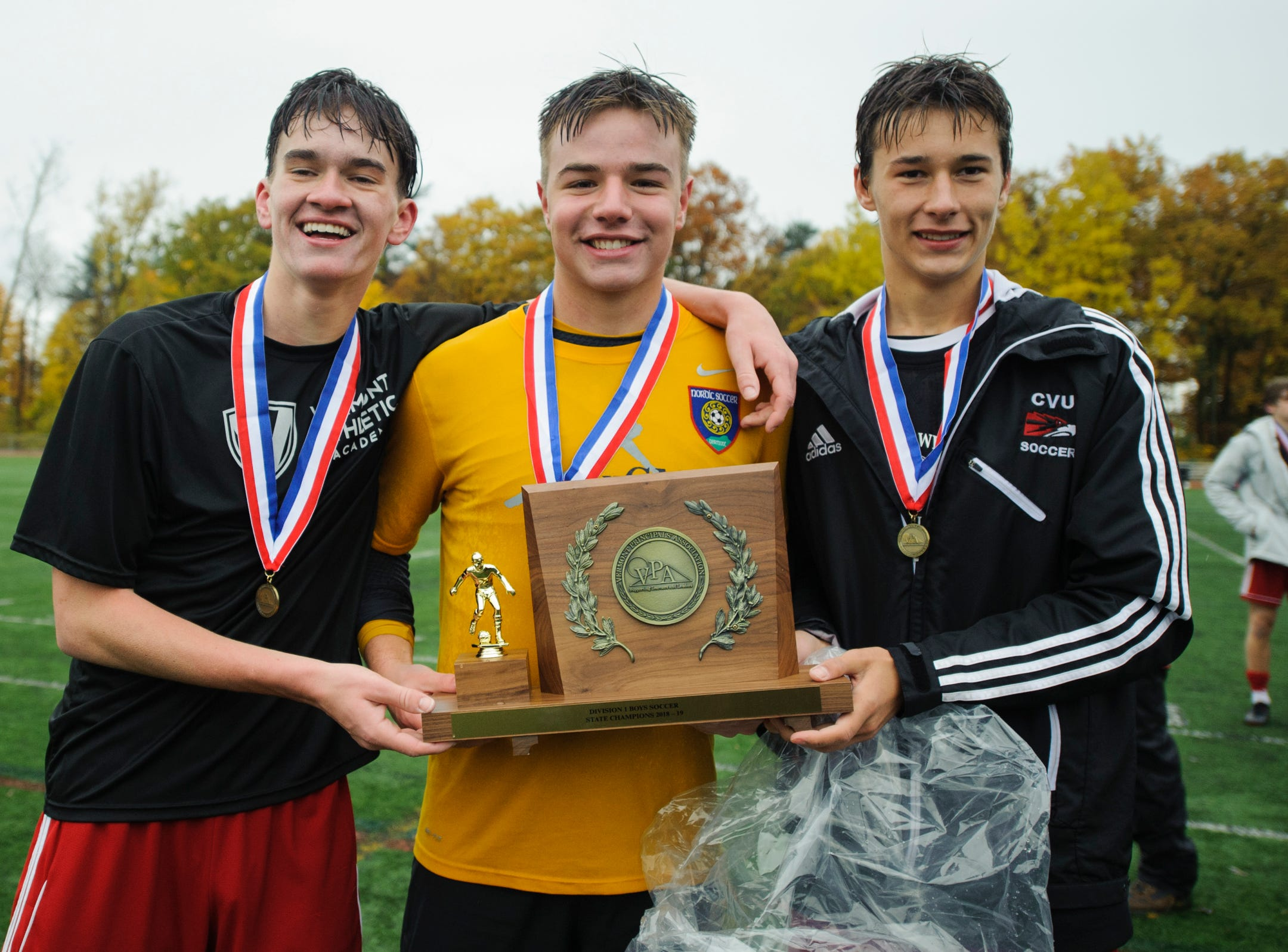 CVU captains hold the championship trophy during the Division I boys soccer championship game between the St. Johnsbury Hilltoppers and the Champlain Valley Union Redhawks at Buck Hard Field on Saturday morning November 3, 2018 in Burlington.