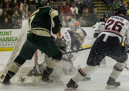 UVM #7 Liam Coughlin keeps the pressure on Uconn goalie #30 Adam Huska after he saved a shot during their hockey game Friday night, Nov. 2, 2018, at home. The Huskies pulled out a win, 1-0.