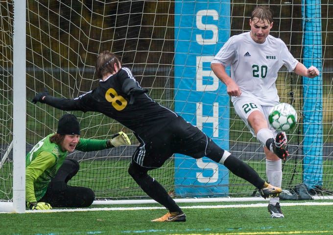 Woodstock #20 Lucas Piconi clears the ball just before Harwood #8 Markus Baird tries to covert a deflected shot by Woodstock goalie Stephen Bianchi during their Div. 2 Vermont State high school boy's soccer championship game at South Burlington High School on Saturday, Nov. 3, 2018. Hardwood Union won, 3-0.