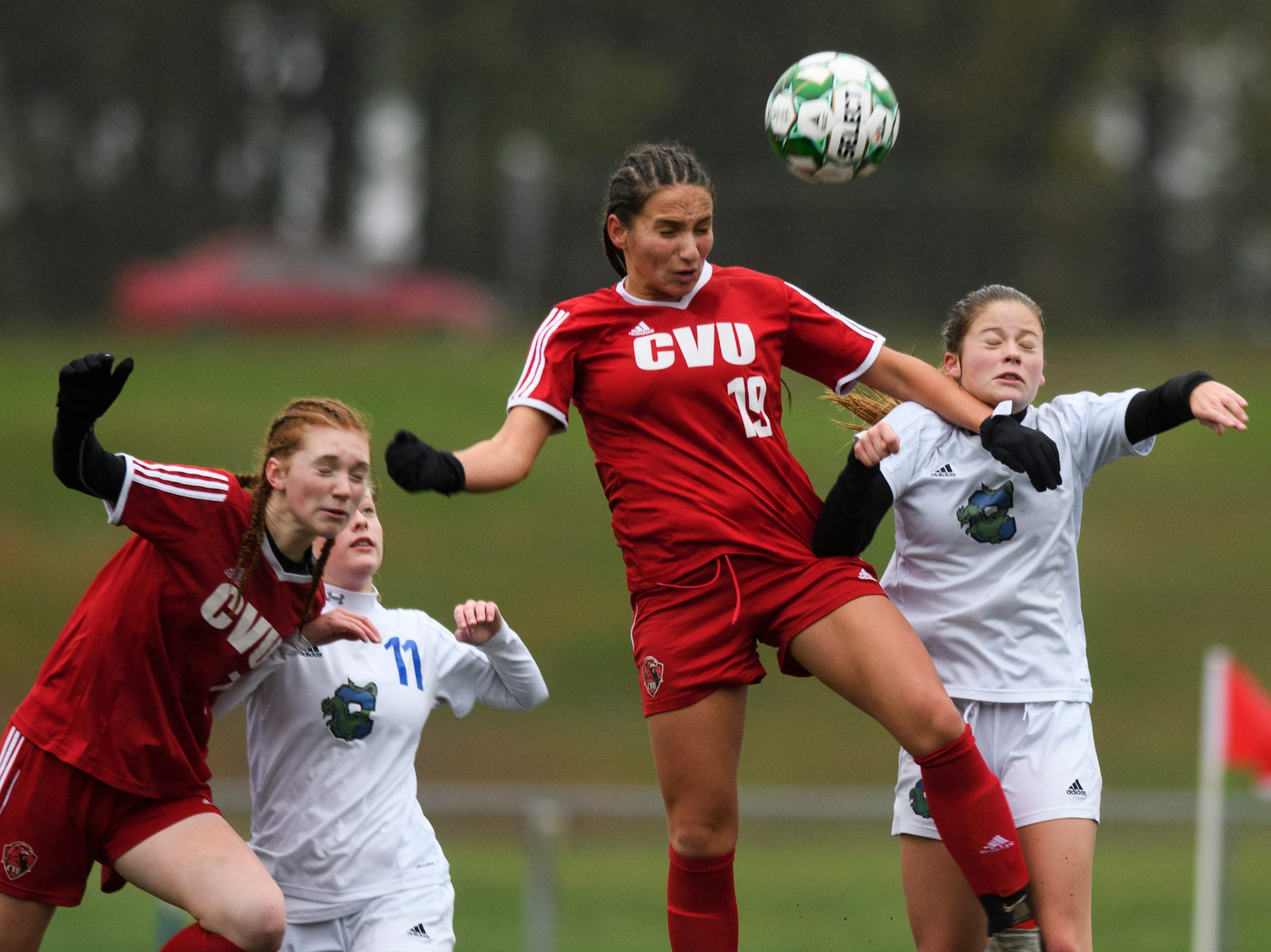 CVU's Sara Kelley (19) leaps over Colchester's Madison Finelli (1) to head the ball during the division I girls soccer championship game between the Colchester Lakers and the Champlain Valley Union Redhawks at Buck Hard Field on Saturday morning November 3, 2018 in Burlington.
