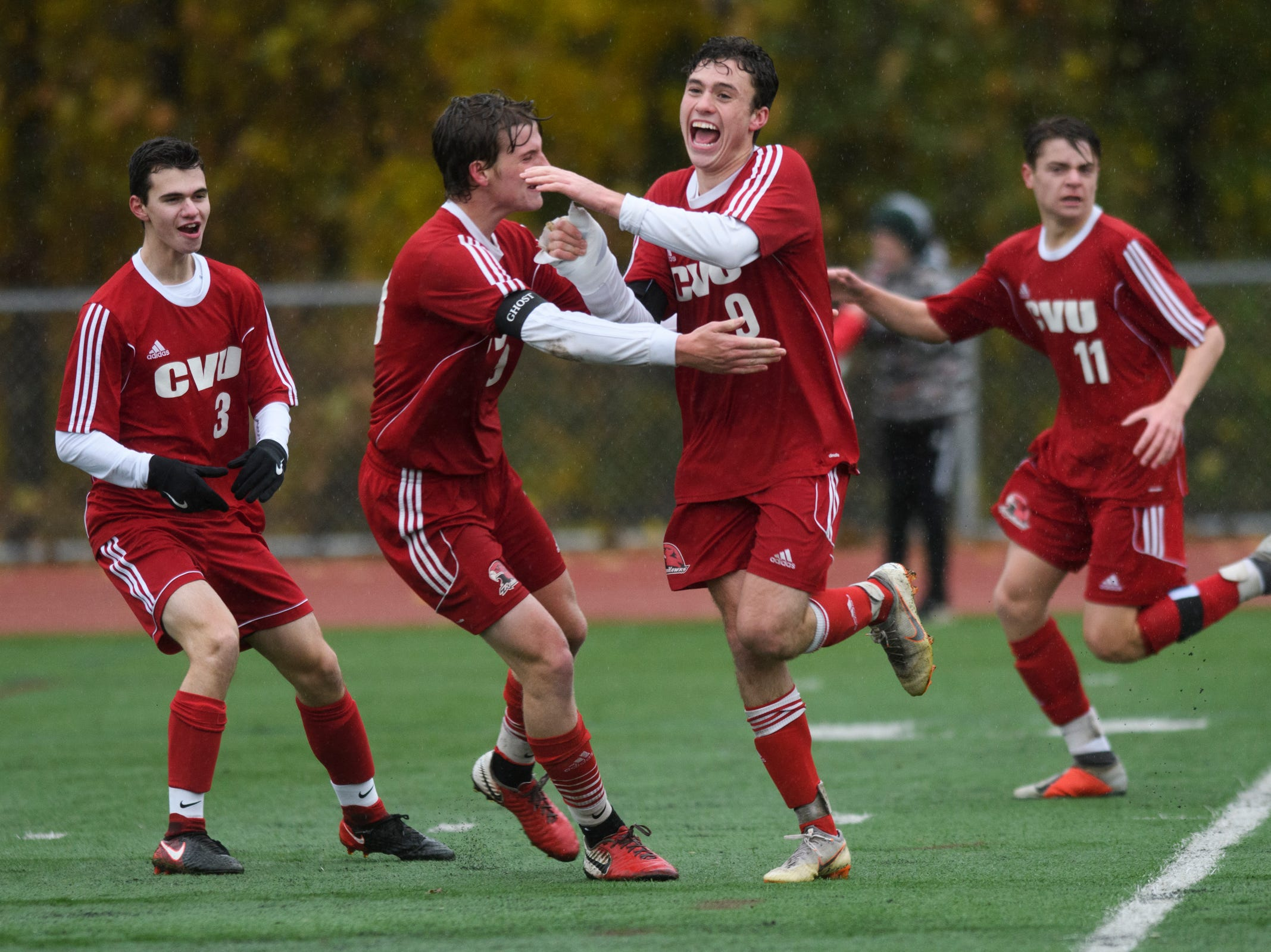 CVU's Jonah Roberts (9), Enzo Delia (8), Caleb Martin (11) and Jacob Allaire (3) celebrate a goal during the Division I boys soccer championship game between the St. Johnsbury Hilltoppers and the Champlain Valley Union Redhawks at Buck Hard Field on Saturday morning November 3, 2018 in Burlington.