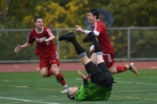 CVU's Jonah Roberts (9) and Caleb Martin celebrates a goal as the referee falls down during the Division I boys soccer championship game between the St. Johnsbury Hilltoppers and the Champlain Valley Union Redhawks at Buck Hard Field on Saturday morning November 3, 2018 in Burlington.