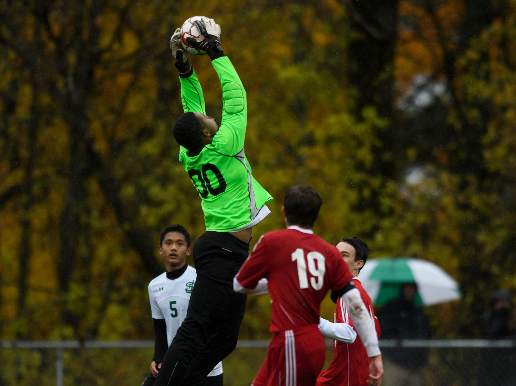 St. Johnsbury goalie Asom Hayman-Jones (00) leaps to make a save during the Division I boys soccer championship game between the St. Johnsbury Hilltoppers and the Champlain Valley Union Redhawks at Buck Hard Field on Saturday morning November 3, 2018 in Burlington.