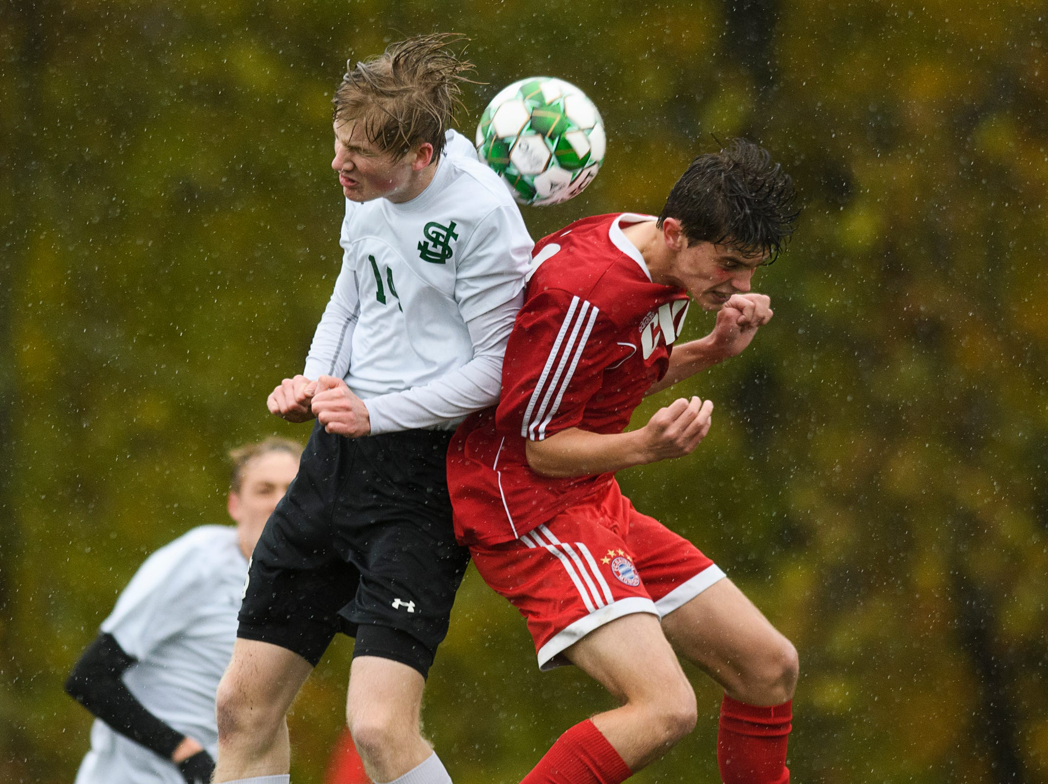 CVU's Jack Sinopoli (30) and St. Johnsbury's Liam Tobin (14) battle to head the ball during the Division I boys soccer championship game between the St. Johnsbury Hilltoppers and the Champlain Valley Union Redhawks at Buck Hard Field on Saturday morning November 3, 2018 in Burlington.