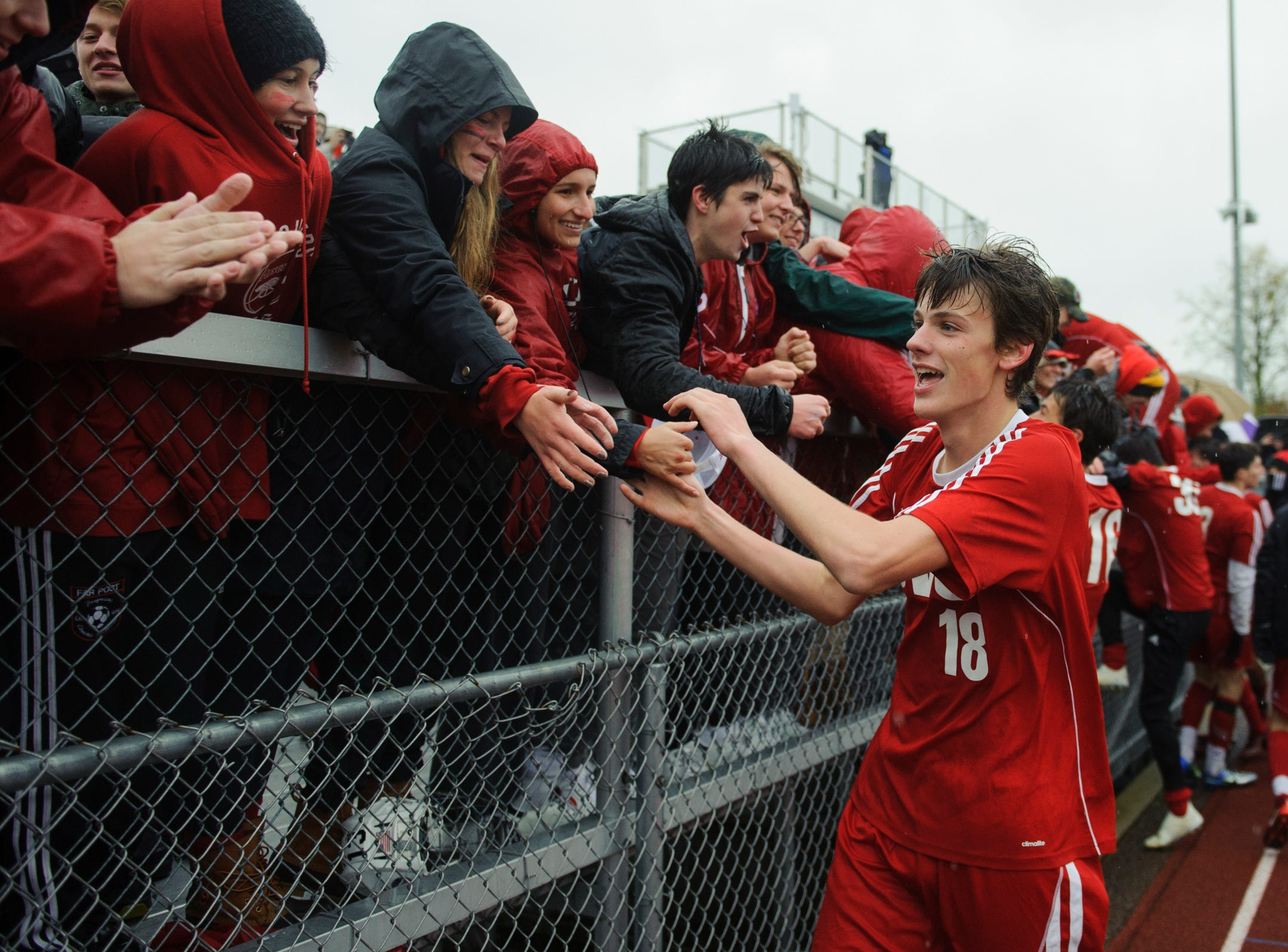 CVU's Benjamin Ross (18) high fives fans in celebration during the Division I boys soccer championship game between the St. Johnsbury Hilltoppers and the Champlain Valley Union Redhawks at Buck Hard Field on Saturday morning November 3, 2018 in Burlington.