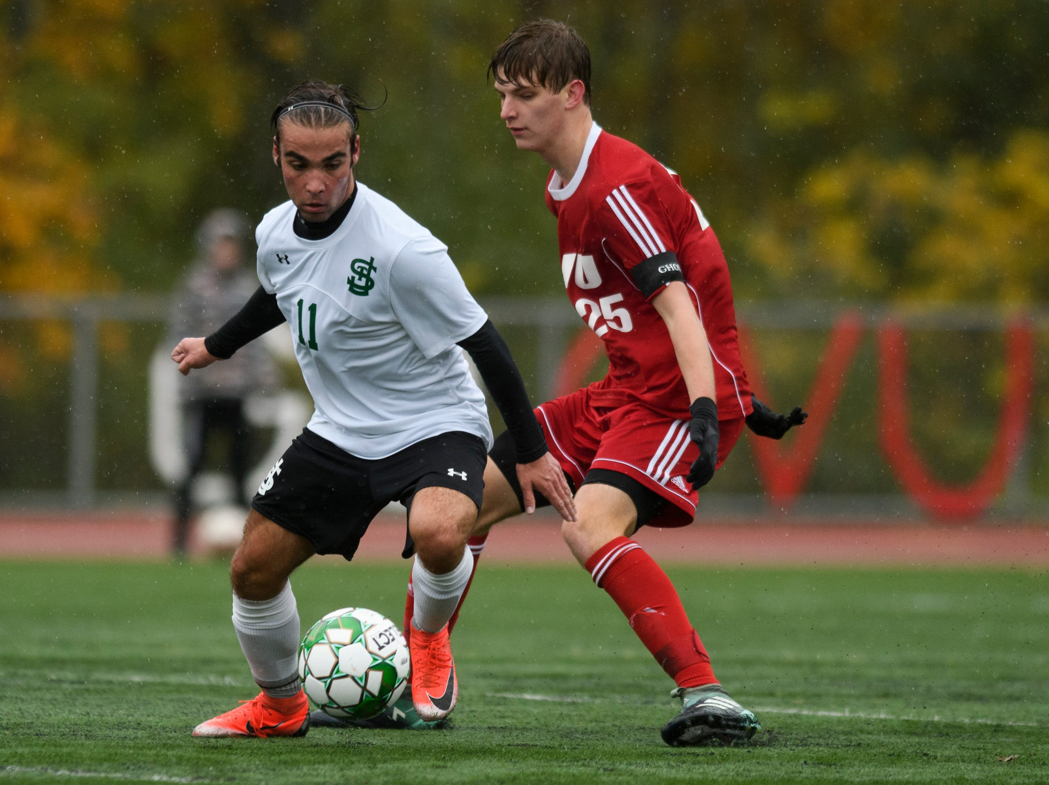 St. Johnsbury's Pablo Gonzales-Rotger (11) plays the ball past CVU's Cullen Sweet (25) during the Division I boys soccer championship game between the St. Johnsbury Hilltoppers and the Champlain Valley Union Redhawks at Buck Hard Field on Saturday morning November 3, 2018 in Burlington.