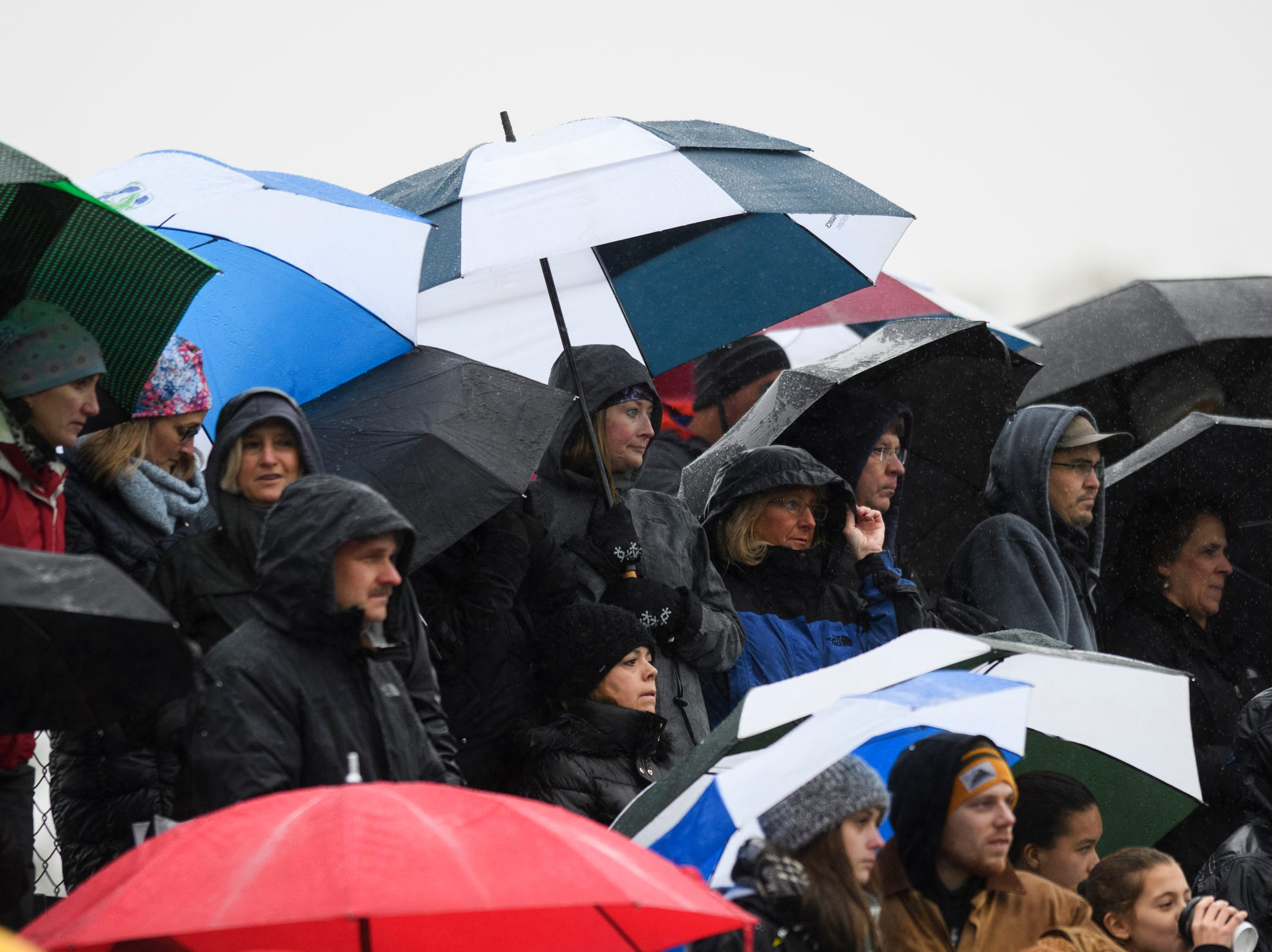 Parents and fans watch the action in the pouring rain during the division I girls soccer championship game between the Colchester Lakers and the Champlain Valley Union Redhawks at Buck Hard Field on Saturday morning November 3, 2018 in Burlington.