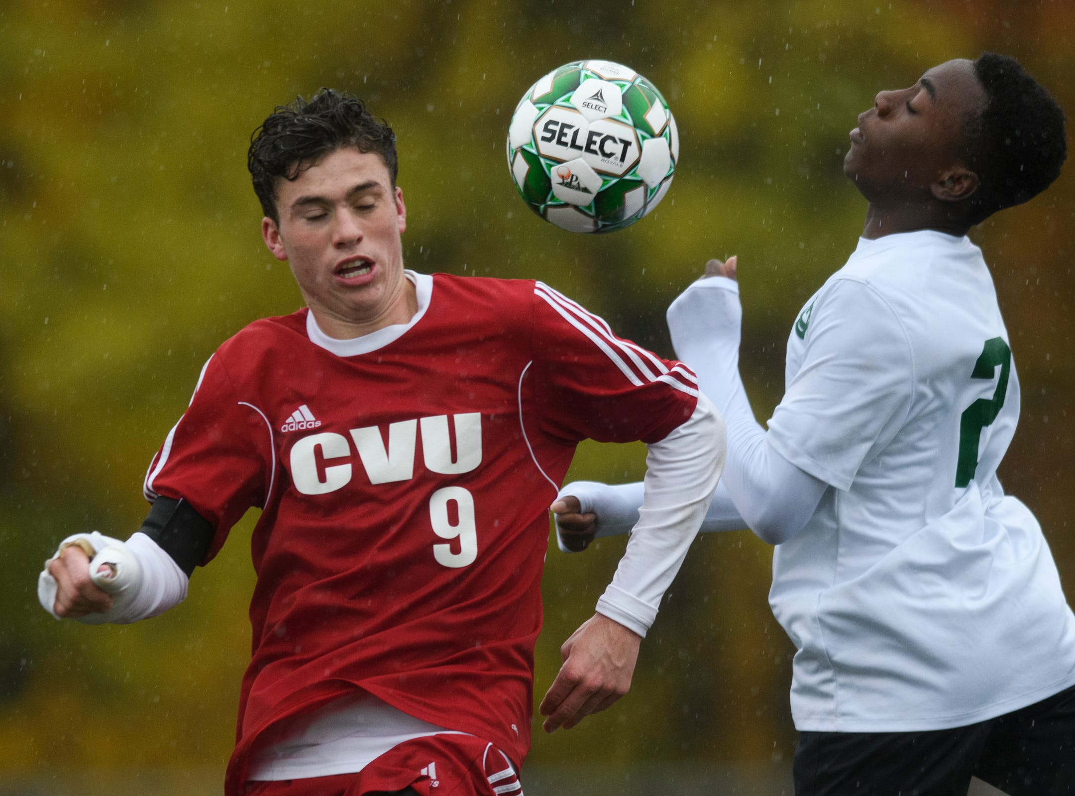 CVU's Jonah Roberts (9) and St. Johnsbury's Denzel Ebohon (21) battle to head the ball during the Division I boys soccer championship game between the St. Johnsbury Hilltoppers and the Champlain Valley Union Redhawks at Buck Hard Field on Saturday morning November 3, 2018 in Burlington.