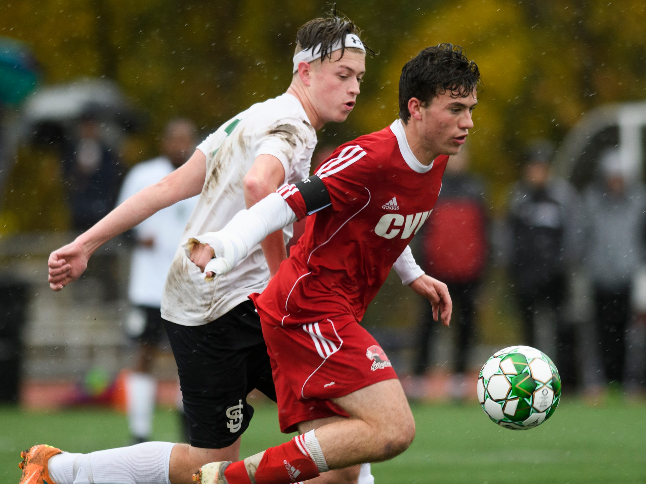 CVU's Jonah Roberts (9) plays the ball past St. Johnsbury's Konard Tillman (7) during the Division I boys soccer championship game between the St. Johnsbury Hilltoppers and the Champlain Valley Union Redhawks at Buck Hard Field on Saturday morning November 3, 2018 in Burlington.