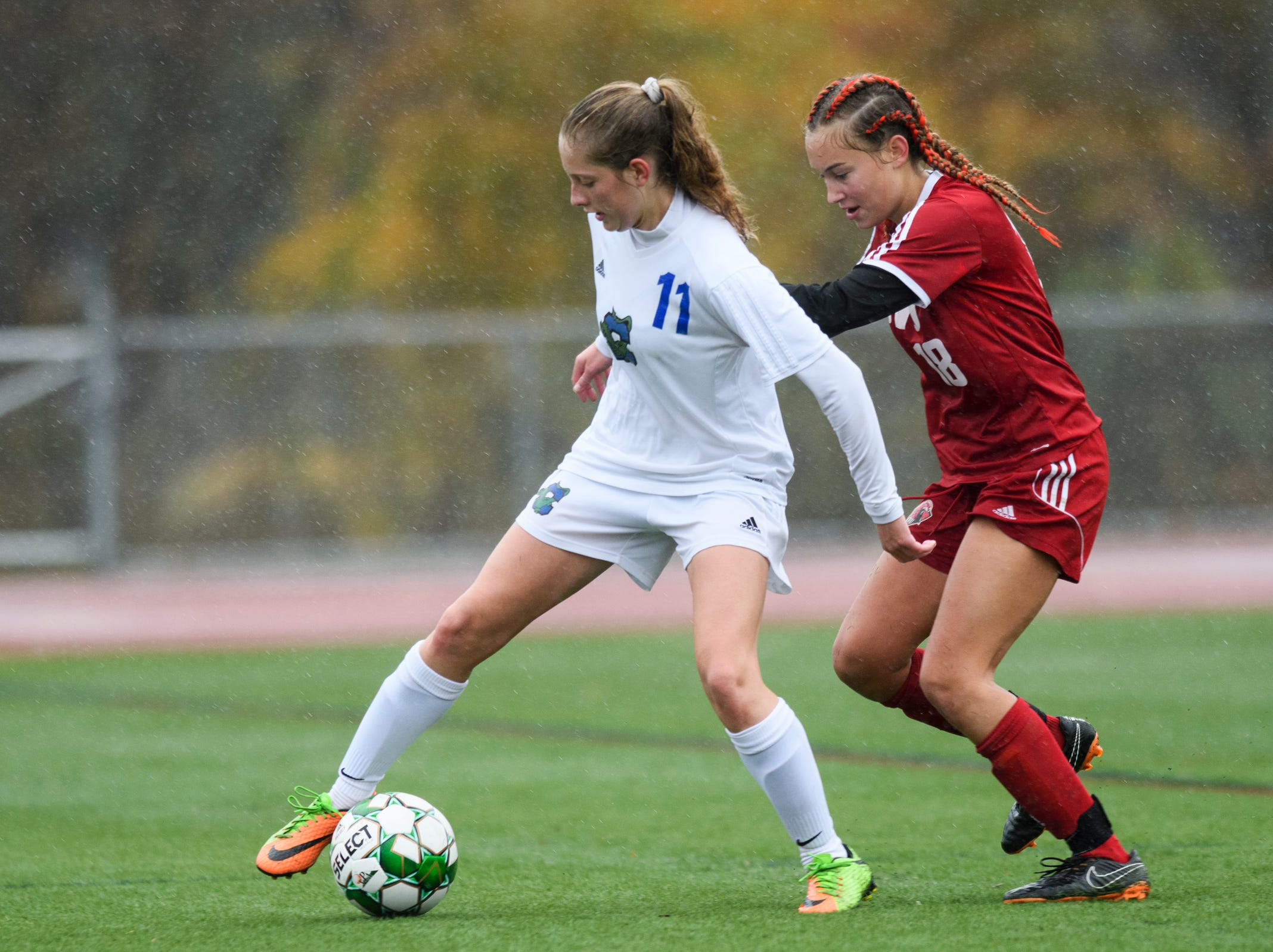 CVU's Elizah Jacobs (18) battles for the ball with Colchester's Jessica Laquerre (11) during the division I girls soccer championship game between the Colchester Lakers and the Champlain Valley Union Redhawks at Buck Hard Field on Saturday morning November 3, 2018 in Burlington.