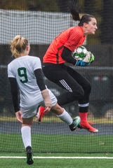 Milton goalie Madison North pulls in the loose ball under pressure from Rice #9 Alex Dostie during the Div. 2 Vermont State girl's high school soccer championship on Saturday, Nov. 3, 2018, at South Burlington High School. Milton won the championship in sudden-death overtime, 2-1.