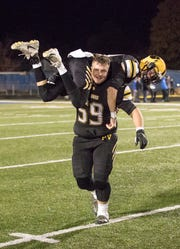Hunter Gibson runs with Patrick Chapman on his shoulders to celebrate Paint Valley's win against Grandview Heights 39-36 in Chillicothe, Ohio.