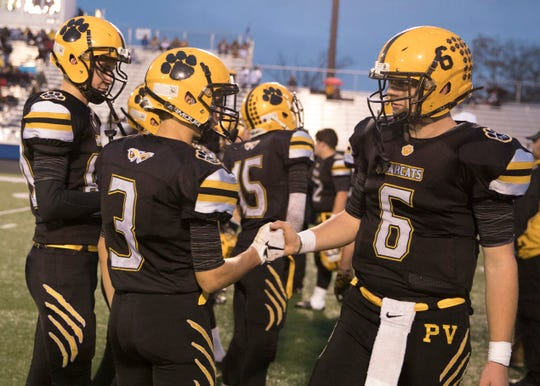 Paint Valley quarterback Bryce Newland shakes hands with teammate Dane Miller during the Bearcats' 39-36 playoff win over Grandview Heights.