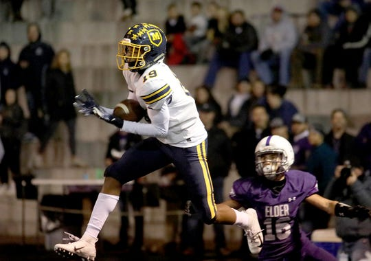 Moeller defensive back Carrington Valentine intercepts a pass  during the Crusaders' playoff game against Elder, Friday, Nov. 2, 2018.