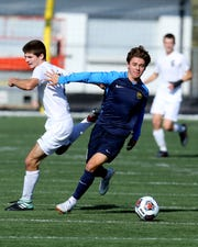 Moeller midfielder Parker Grinstead takes the ball away from Turpin's Max Murphy in the Division I regional final Nov. 3.