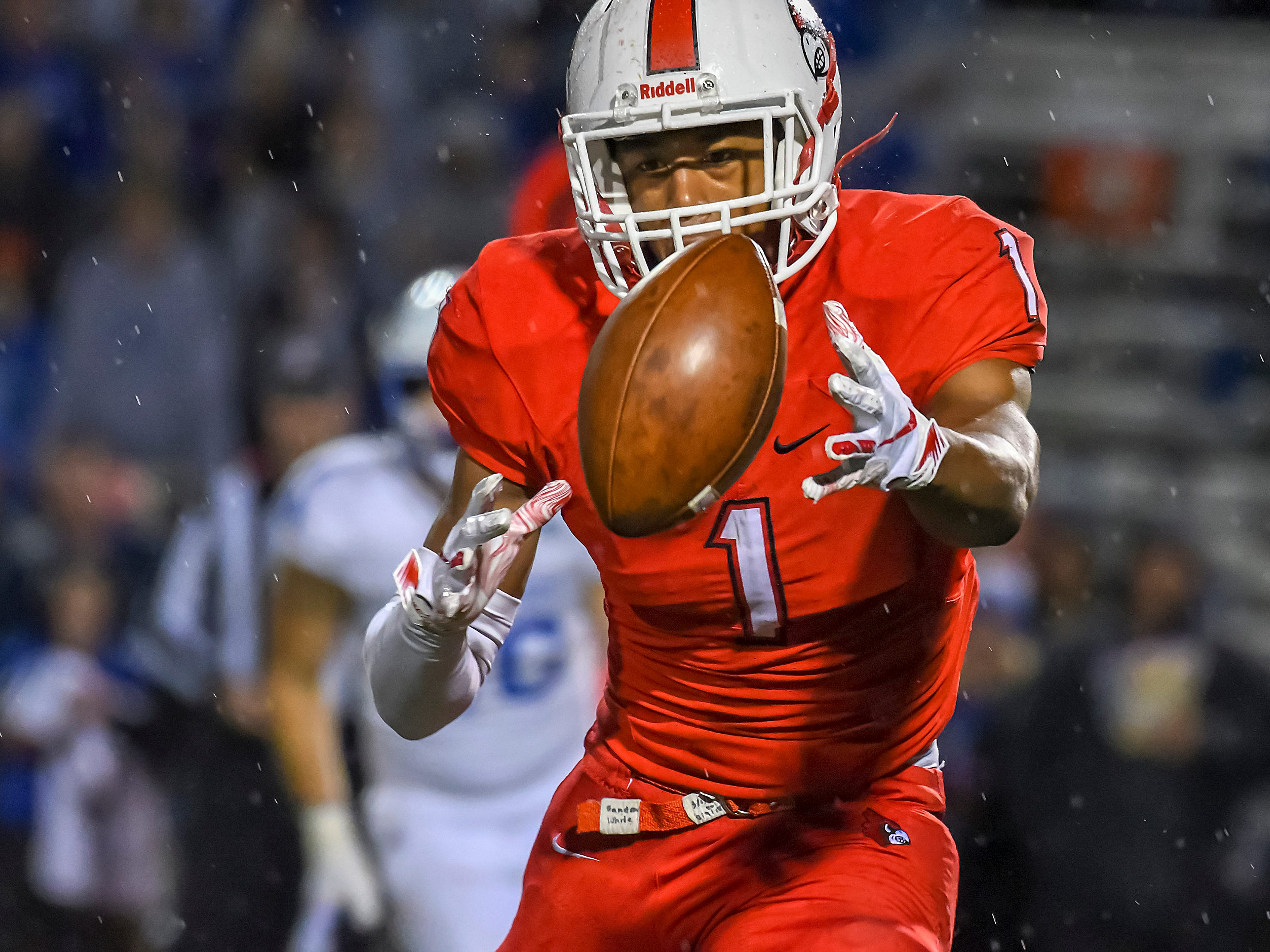 Cardinal running back Syncere Jones bobbles the pitch against St. X in the OHSAA DI Region 4 Playoffs at Colerain High School,  Friday Nov. 2, 2018