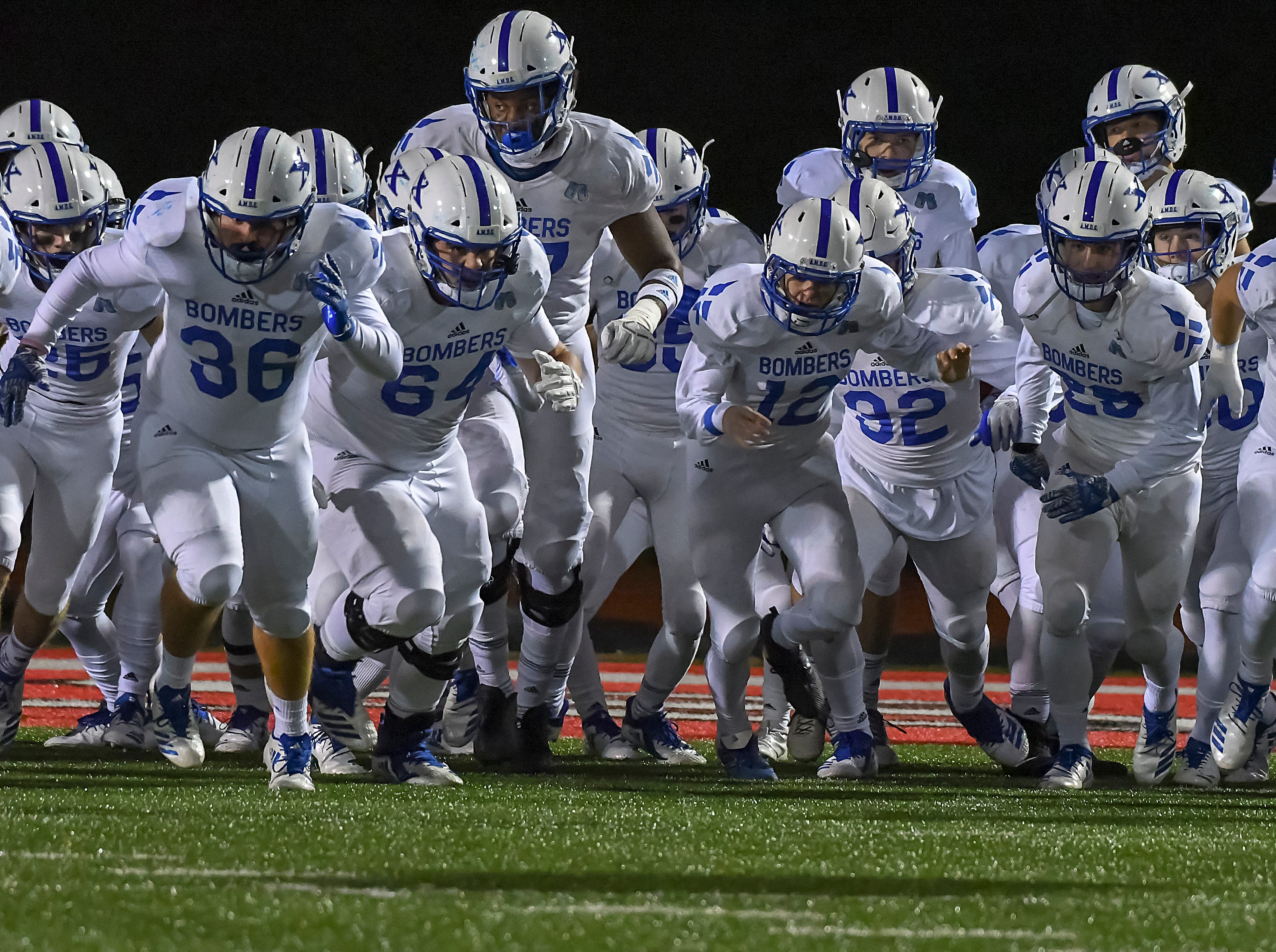 The St. X Bombers run onto the field before their game against Colerain in the OHSAA DI Region 4 Playoffs at Colerain High School,  Friday Nov. 2, 2018