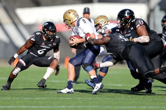 Cincinnati Bearcats defensive end Kimoni Fitz (51) and Cincinnati Bearcats defensive tackle Cortez Broughton (96) tackle Navy Midshipmen quarterback Zach Abey (9) in the second quarter during a college football game between the Navy Midshipmen and the Cincinnati Bearcats, Saturday, Nov. 3, 2018, at Nippert Stadium in Cincinnati.
