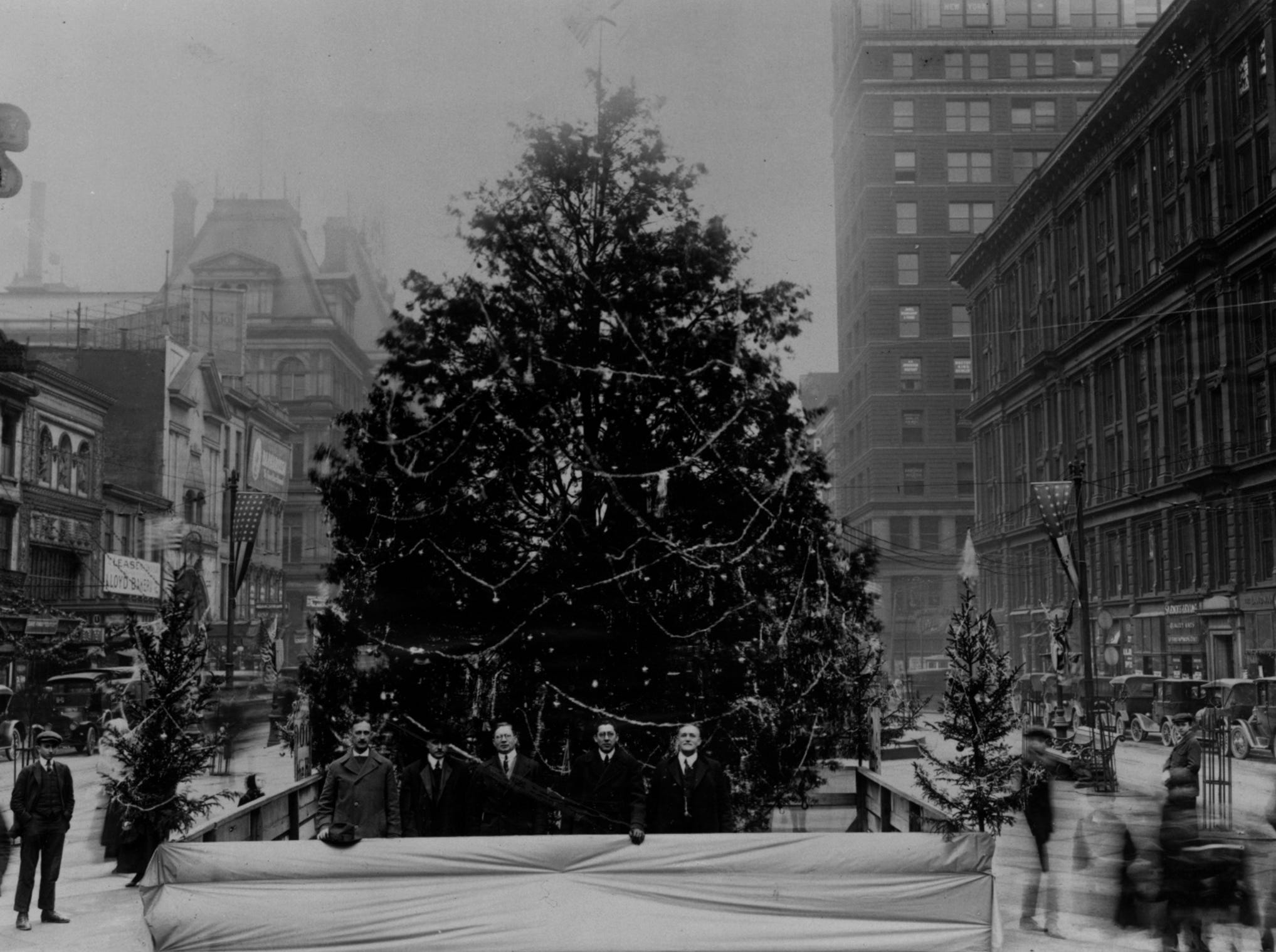 1918: The first municipal Christmas tree appeared on Fountain Square in 1918. City officials gather for the lighting.