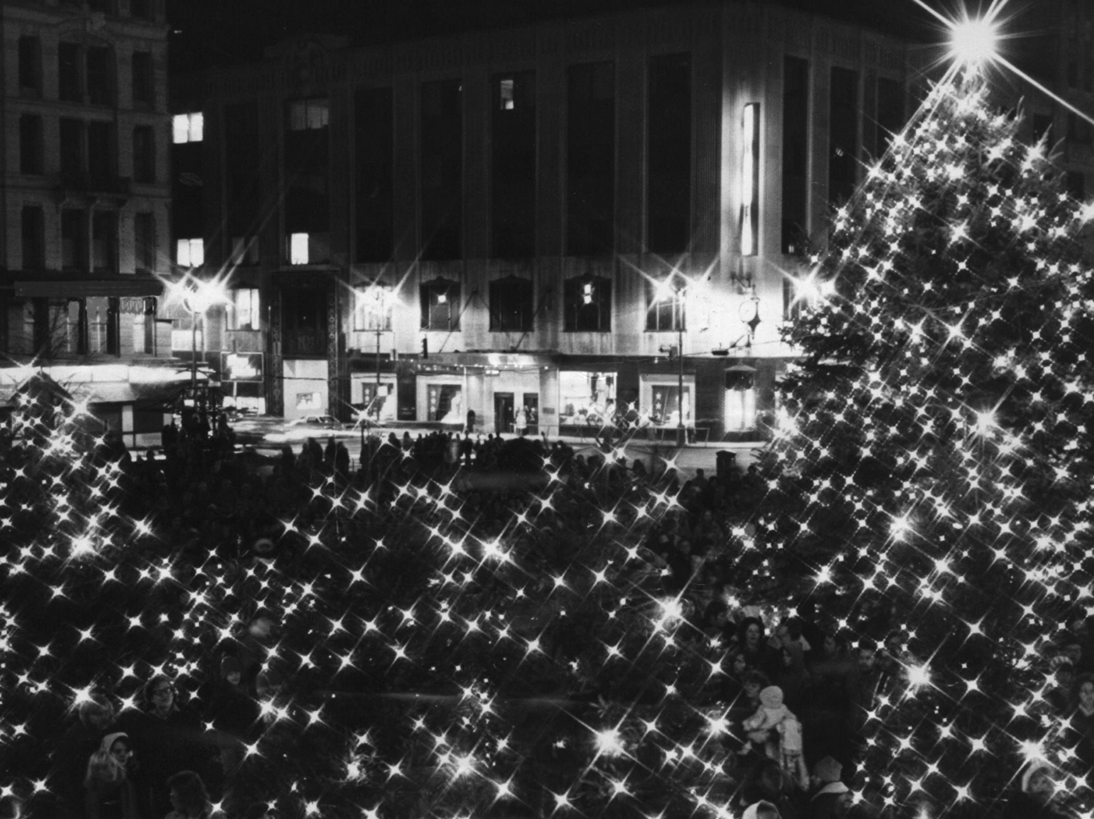 1975: Mayor Theodore M. Berry, accompanied by several Cincinnati Council members, threw the official switch Friday, Nov. 28, and lighted up the Christmas lights strung through the tree branches on Fountain Square.