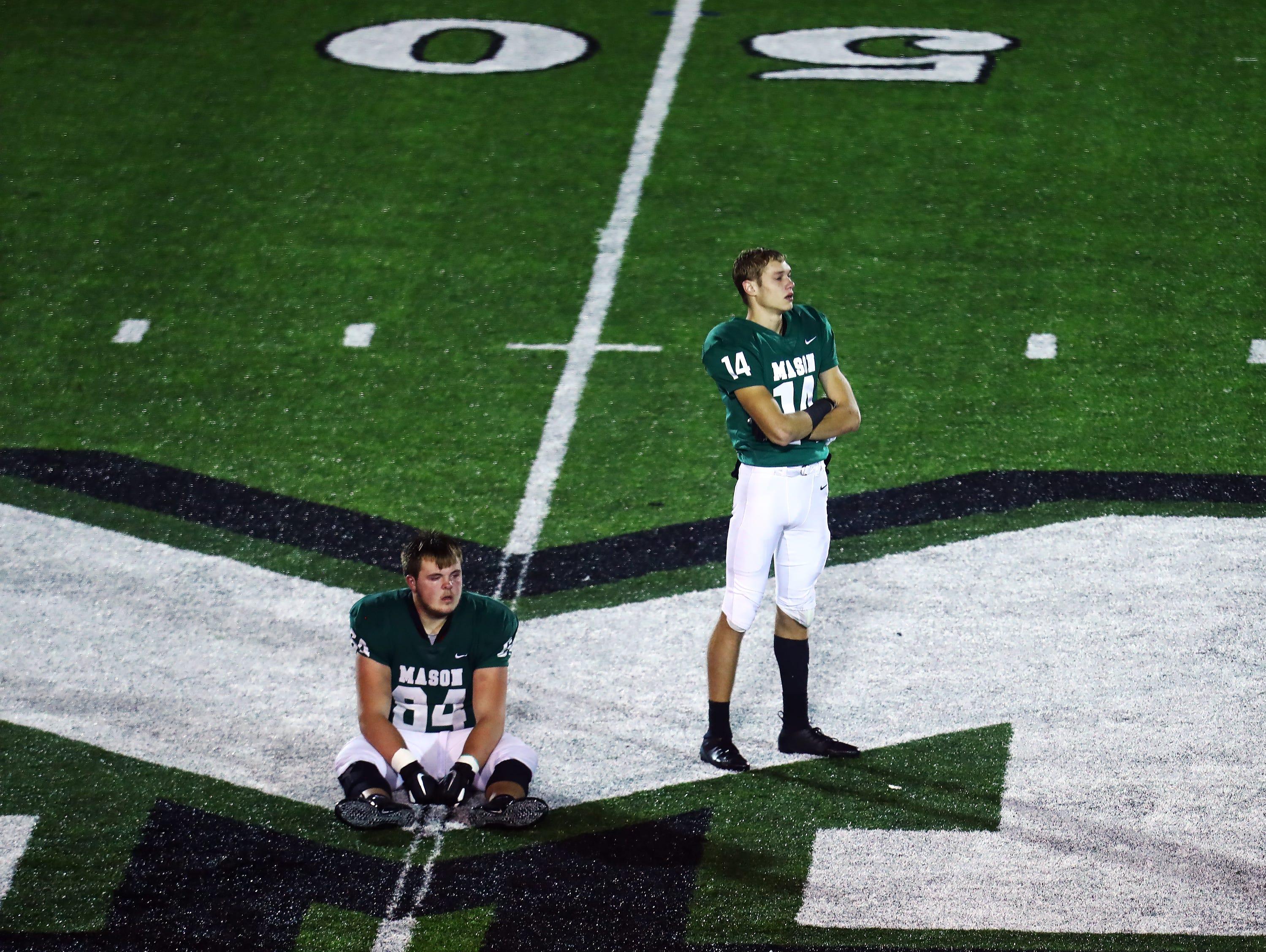 Mason seniors Camden Wood [64] and Jaydon Kauhfold contemplate their last time on the field as Comet football players. Lakota East defeated Mason 20-17.