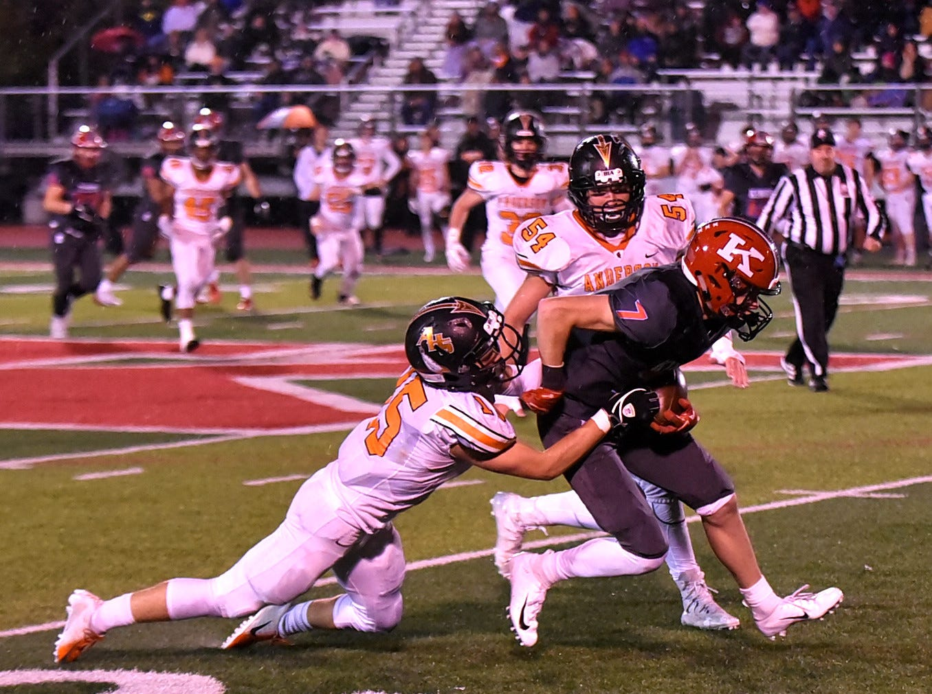 Jack McHugh (7) of Kings picks up first-down yards while dragging the Anderson defense with him in the Division 2 Region quarterfinal playoff game, November 2, 2018.