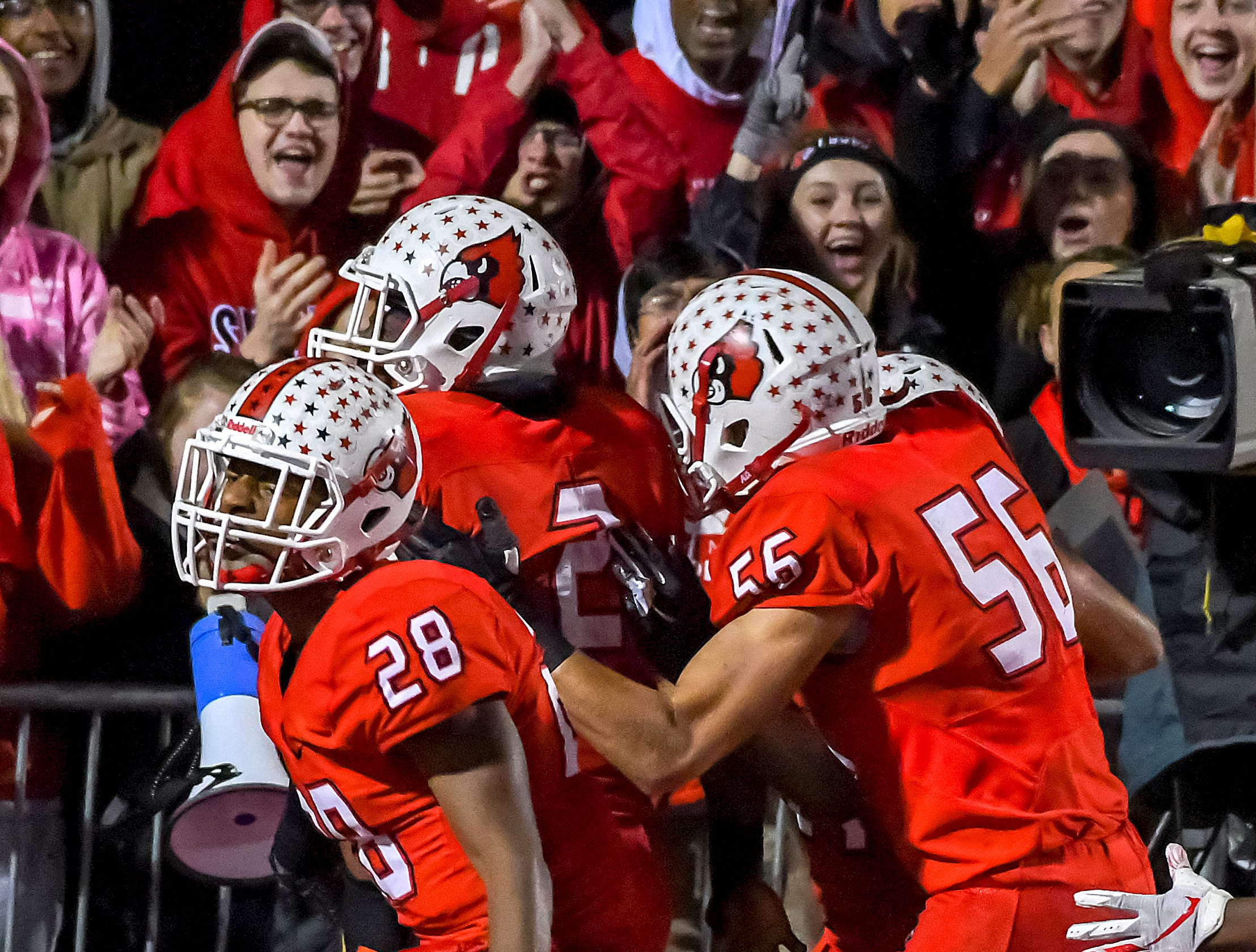 The Colerain Cardinals celebrate after a Deante Smith-Moore touchdown against St. X in the OHSAA DI Region 4 Playoffs at Colerain High School,  Friday Nov. 2, 2018