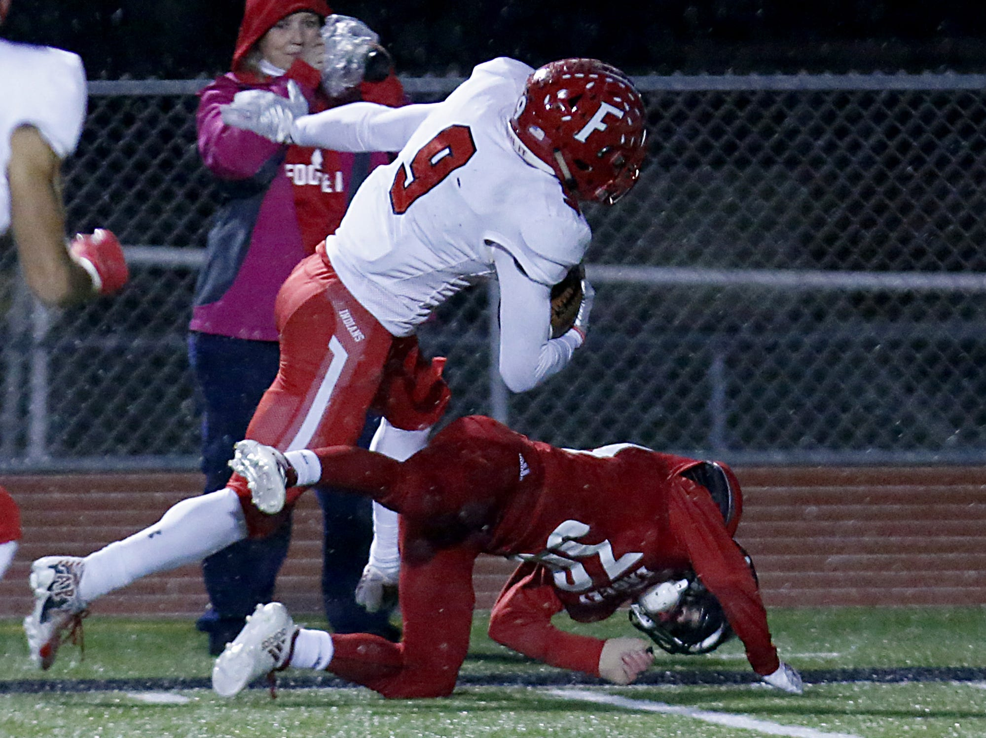 Fairfield running back Jutahn McClain is stopped at the four yard line by Milford defensive back Max Ward during their Division I playoff game at Eagle Stadium in Milford Friday, Nov. 2, 2018.