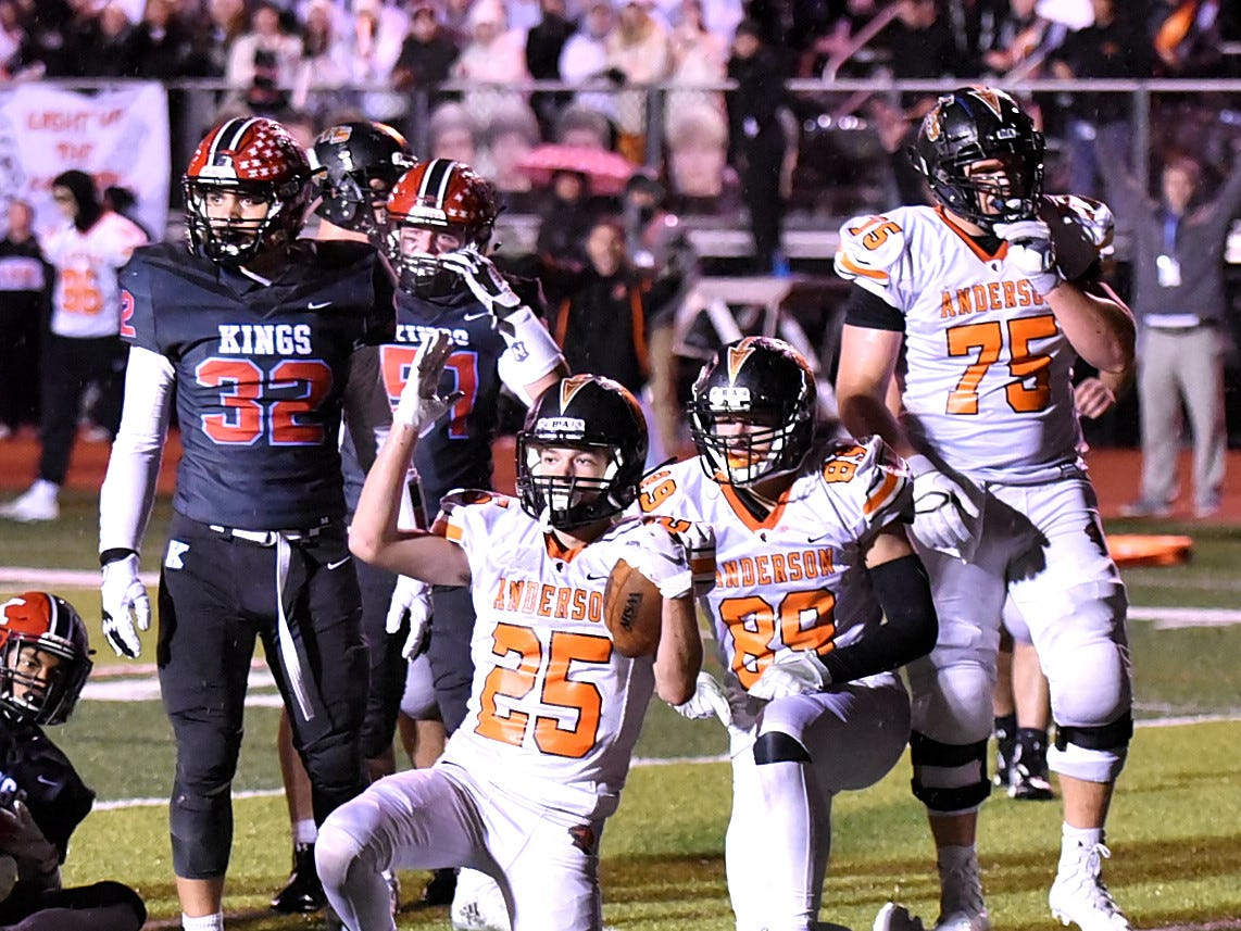 """Bennett Snyder (25) of Anderson signals """"touchdown"""" with his teammates in the Division 2 Region quarterfinal playoff game, November 2, 2018."""