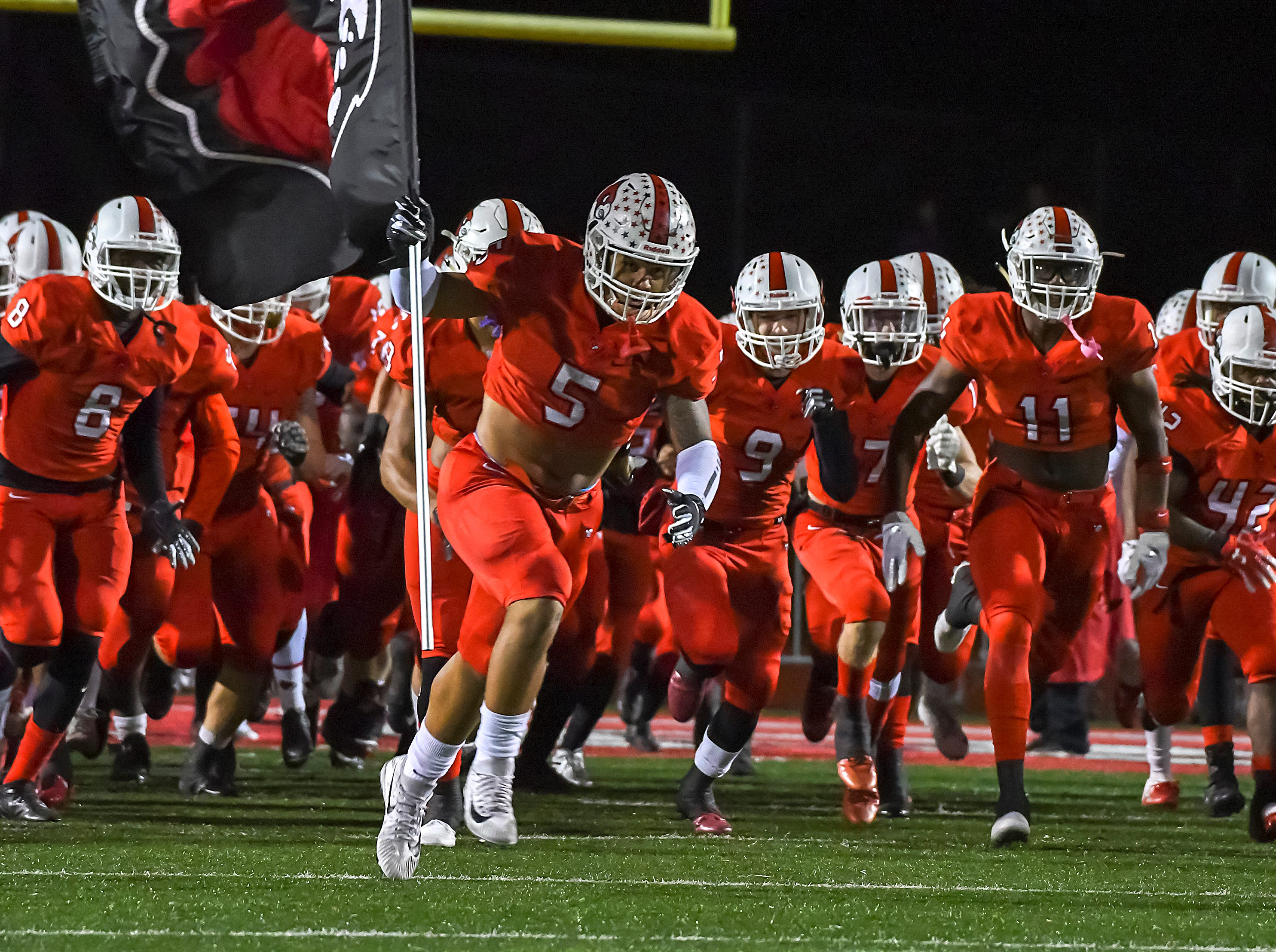 The Colerain Cardinals run onto the field before their game against the St. X Bombers in the OHSAA DI Region 4 Playoffs at Colerain High School,  Friday Nov. 2, 2018