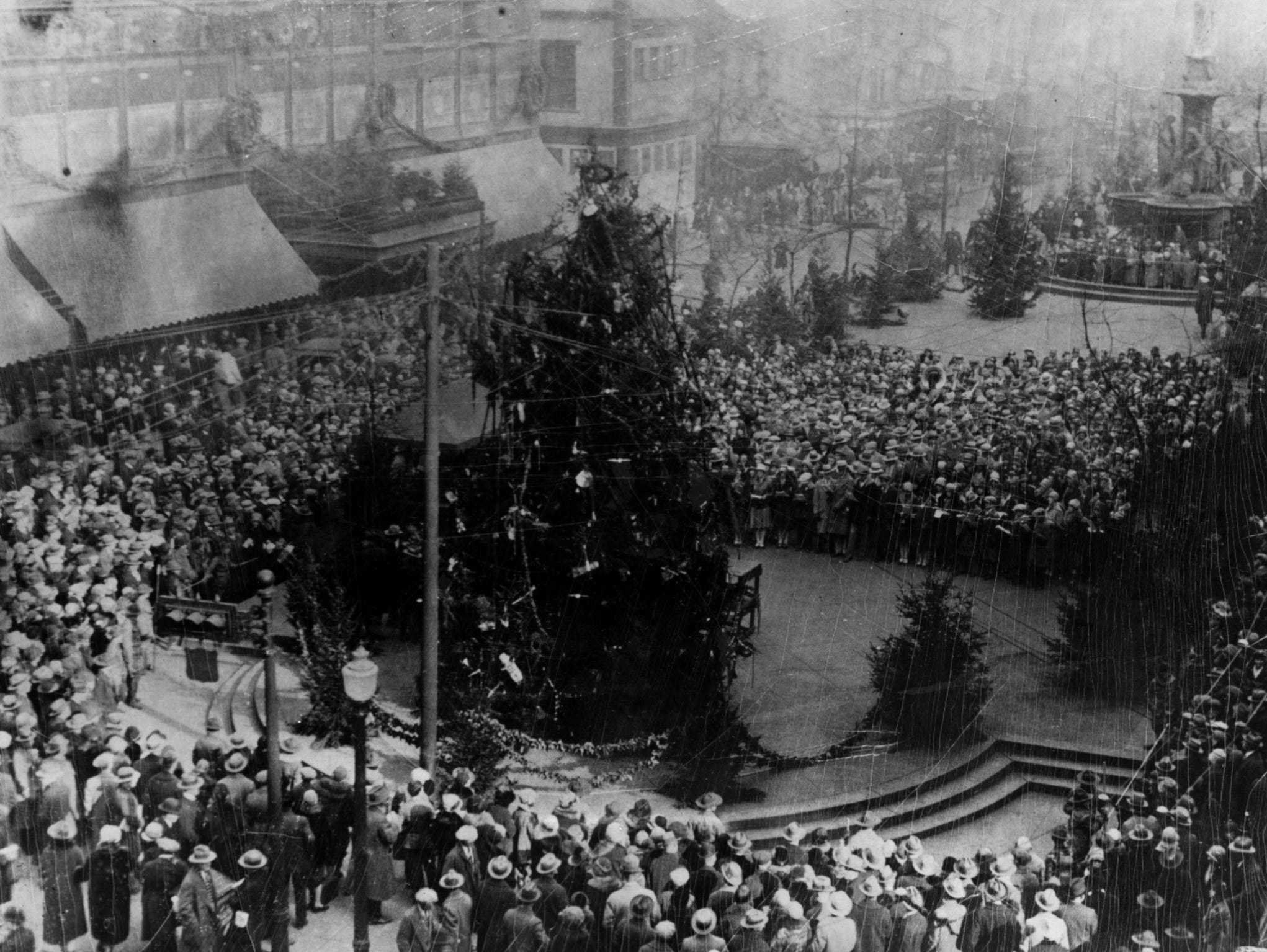 1928: Annual lighting of the Christmas tree on Fountain Square. Hundreds of Cincinnatians gather to officially open the holiday season.