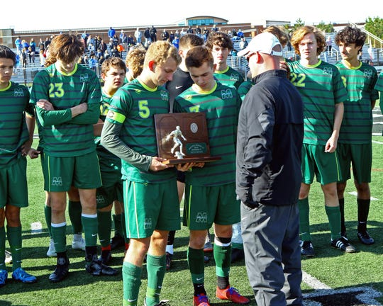 The McNicholas Rockets receive their Runner Up trophy from Lakpota East A.D. Rich Bryant. SCD defeated McNicholas 3-1 to claim the Regional DII Championship.