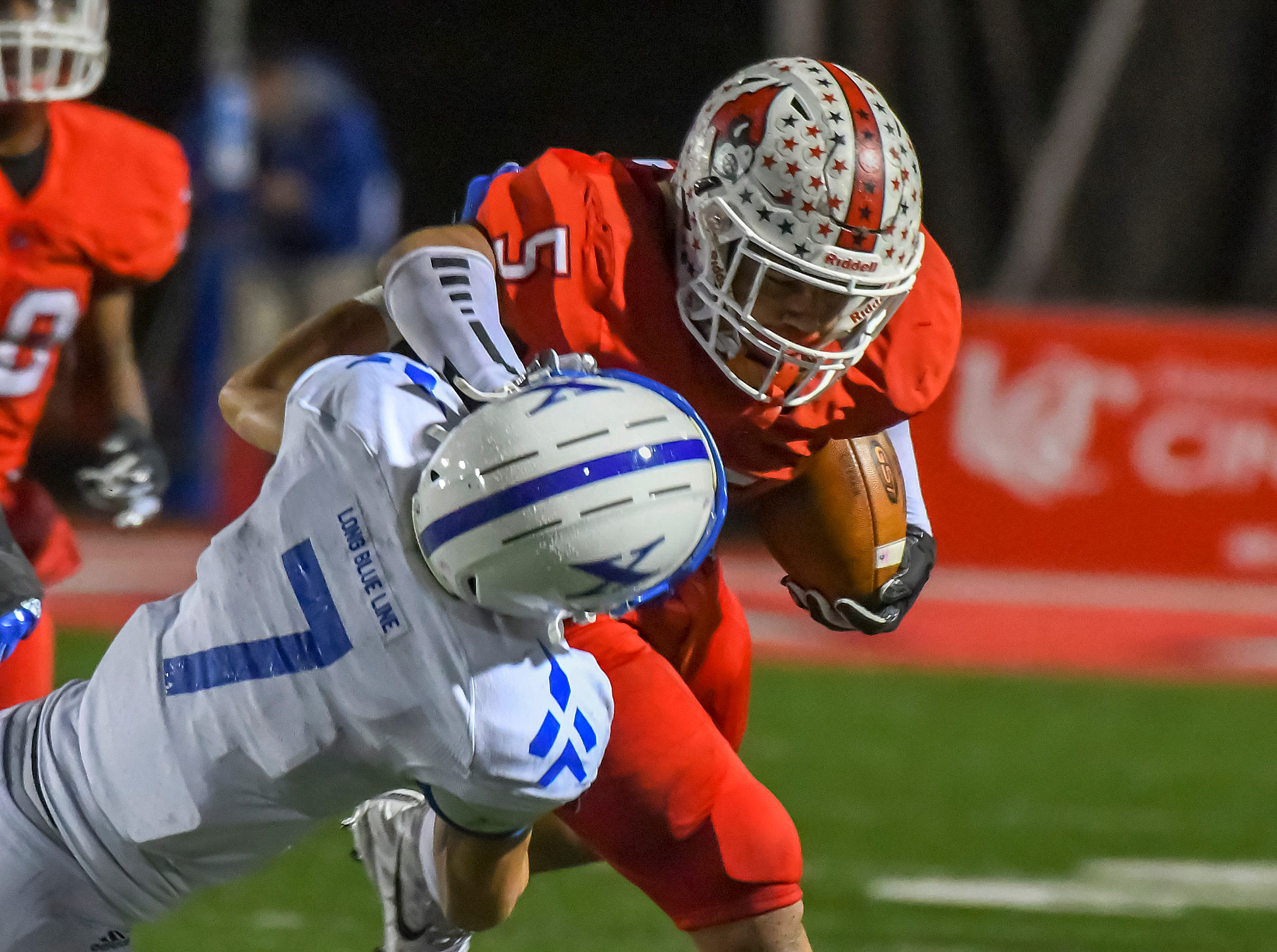 Ivan Pace Jr. of Colerain stiff arms St. X defender Wiles Dolle (7) in the OHSAA DI Region 4 Playoffs at Colerain High School,  Friday Nov. 2, 2018